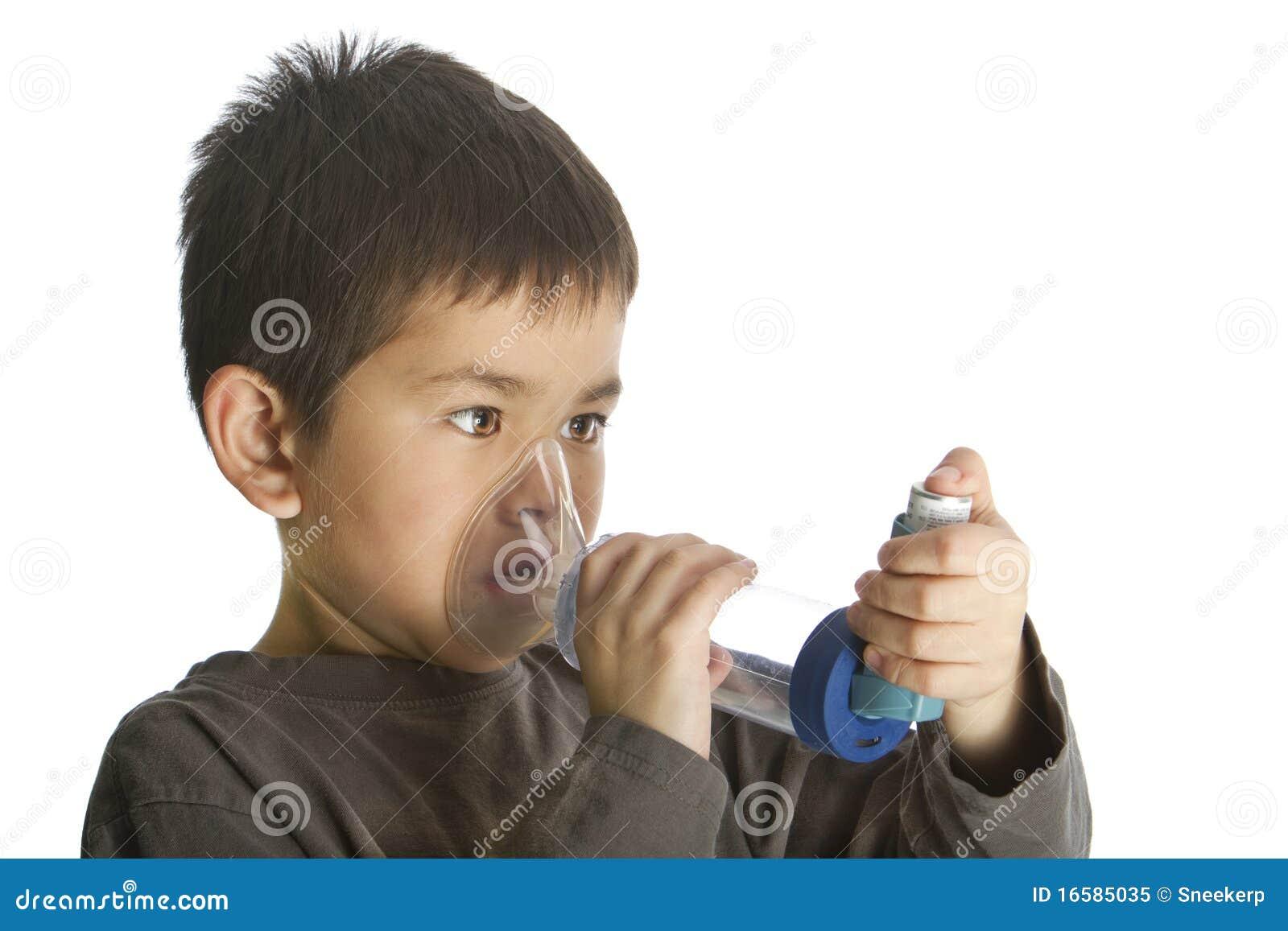 Giovane ragazzo sveglio che per mezzo del suo inalatore di asma