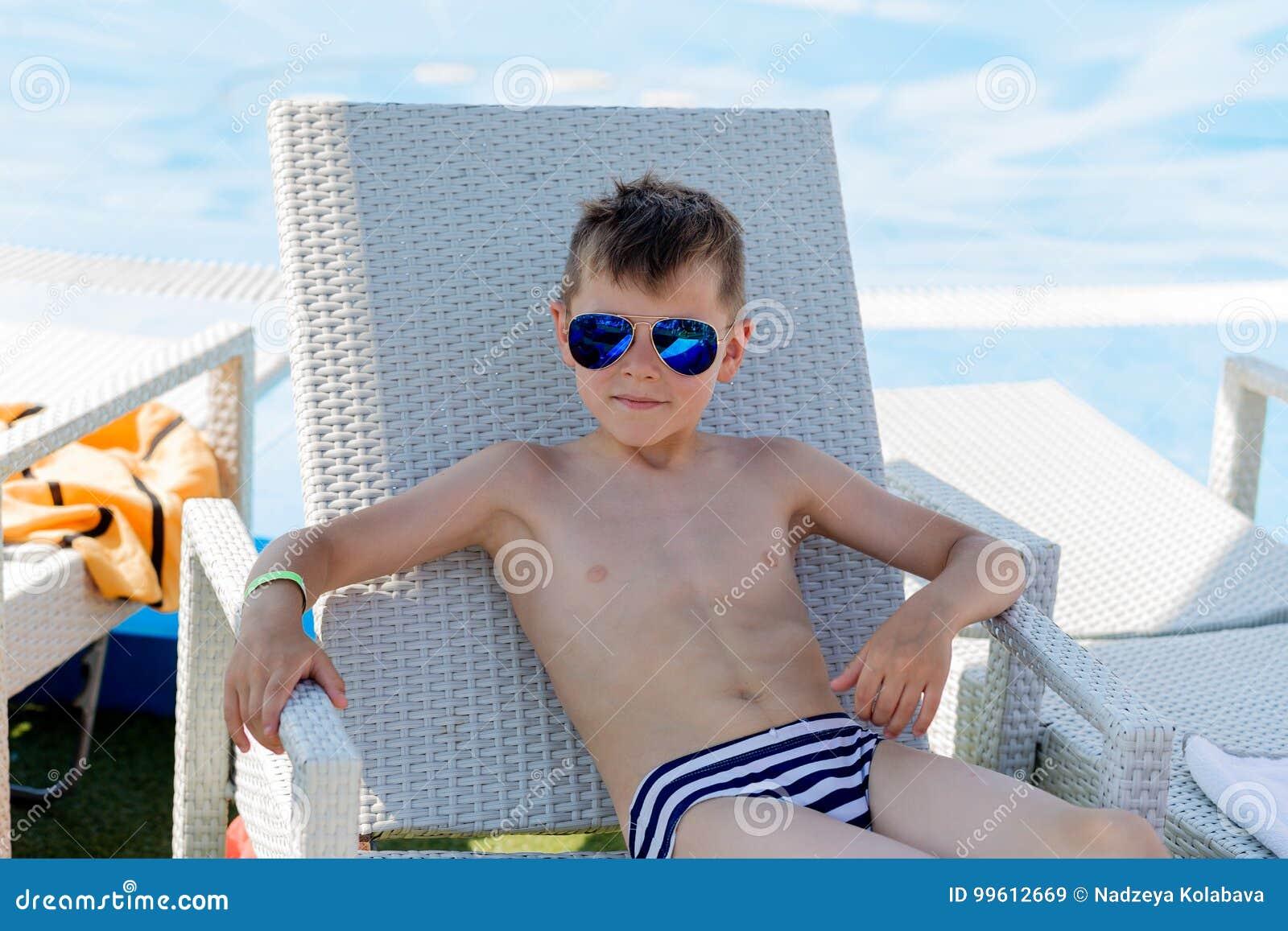 Costume Da Bagno Ragazzo : Giovane ragazzo in un costume da bagno su uno scaffale dallo