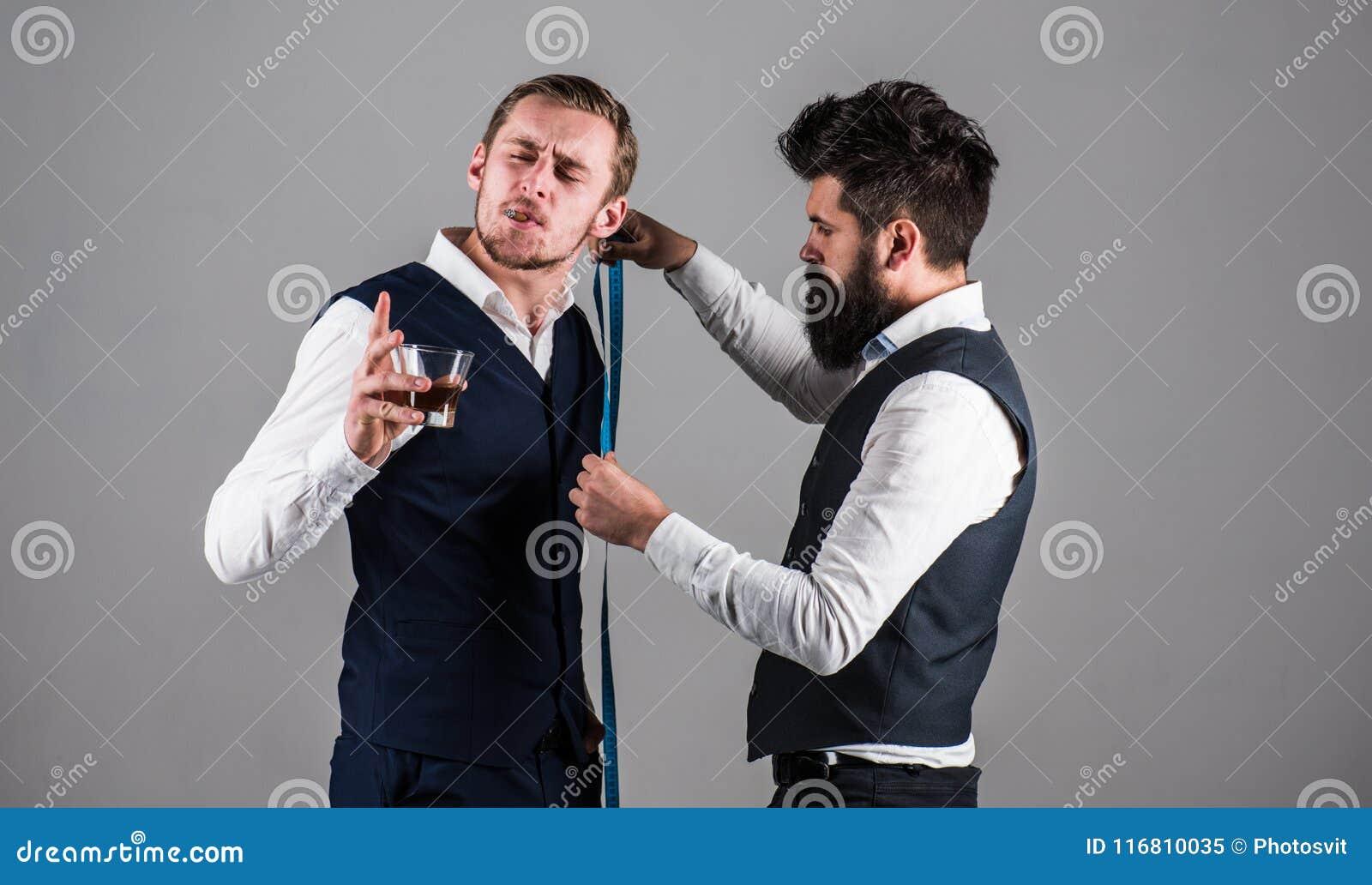 Giovane sarto di visita dell uomo d affari Uomo con la barba occupata con la misurazione