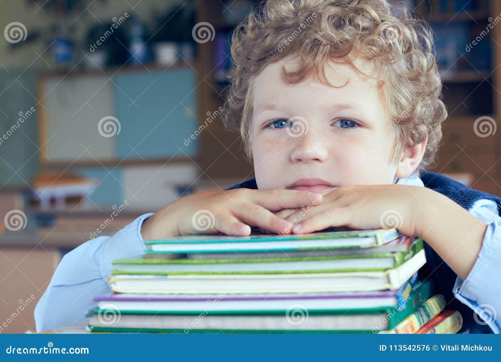 Giovane scolaro caucasico sveglio che si trova sopra un mucchio dei libri all aula