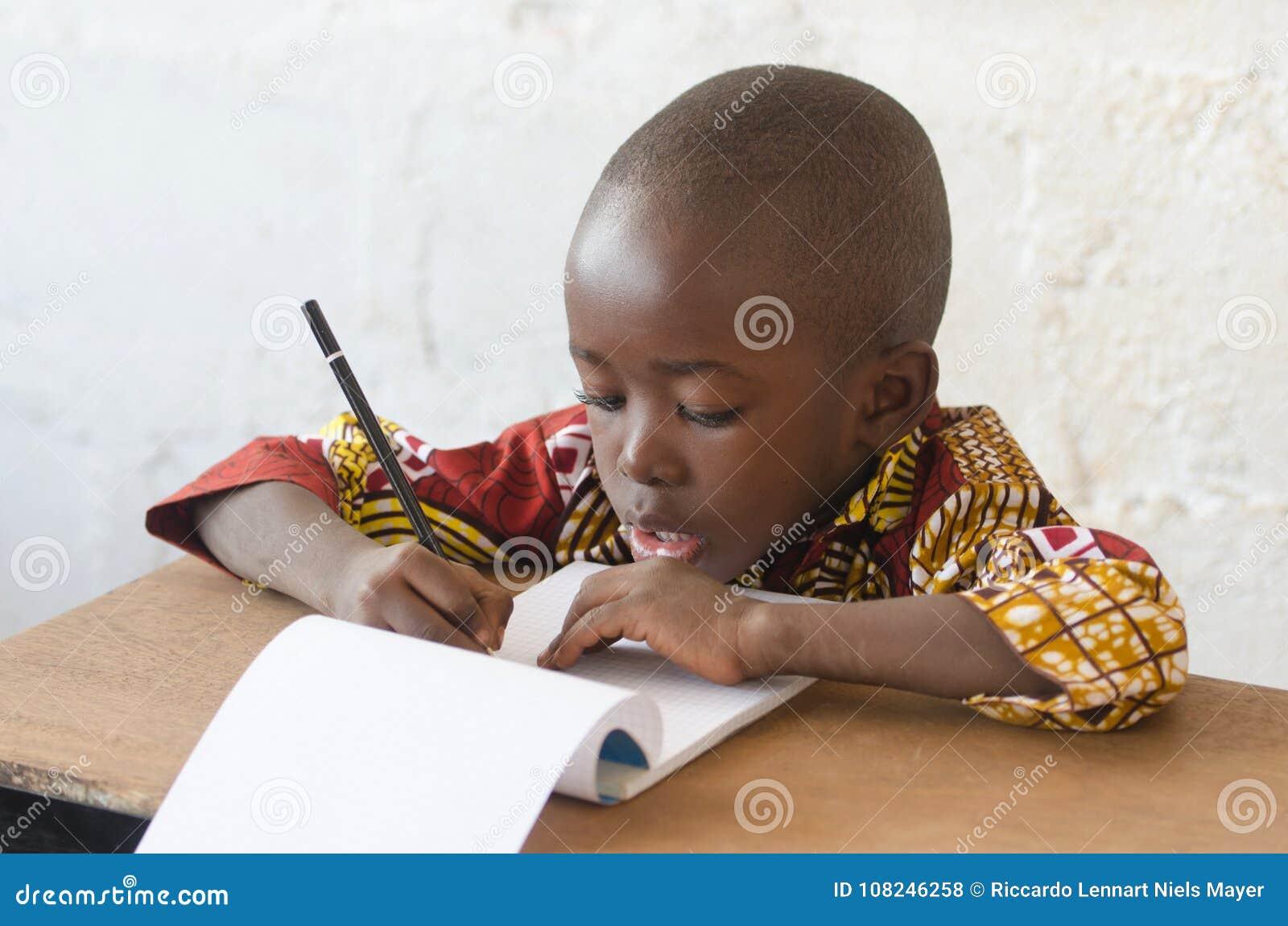 Giovane scrittura africana bella del ragazzo ed imparare a scuola Buildi
