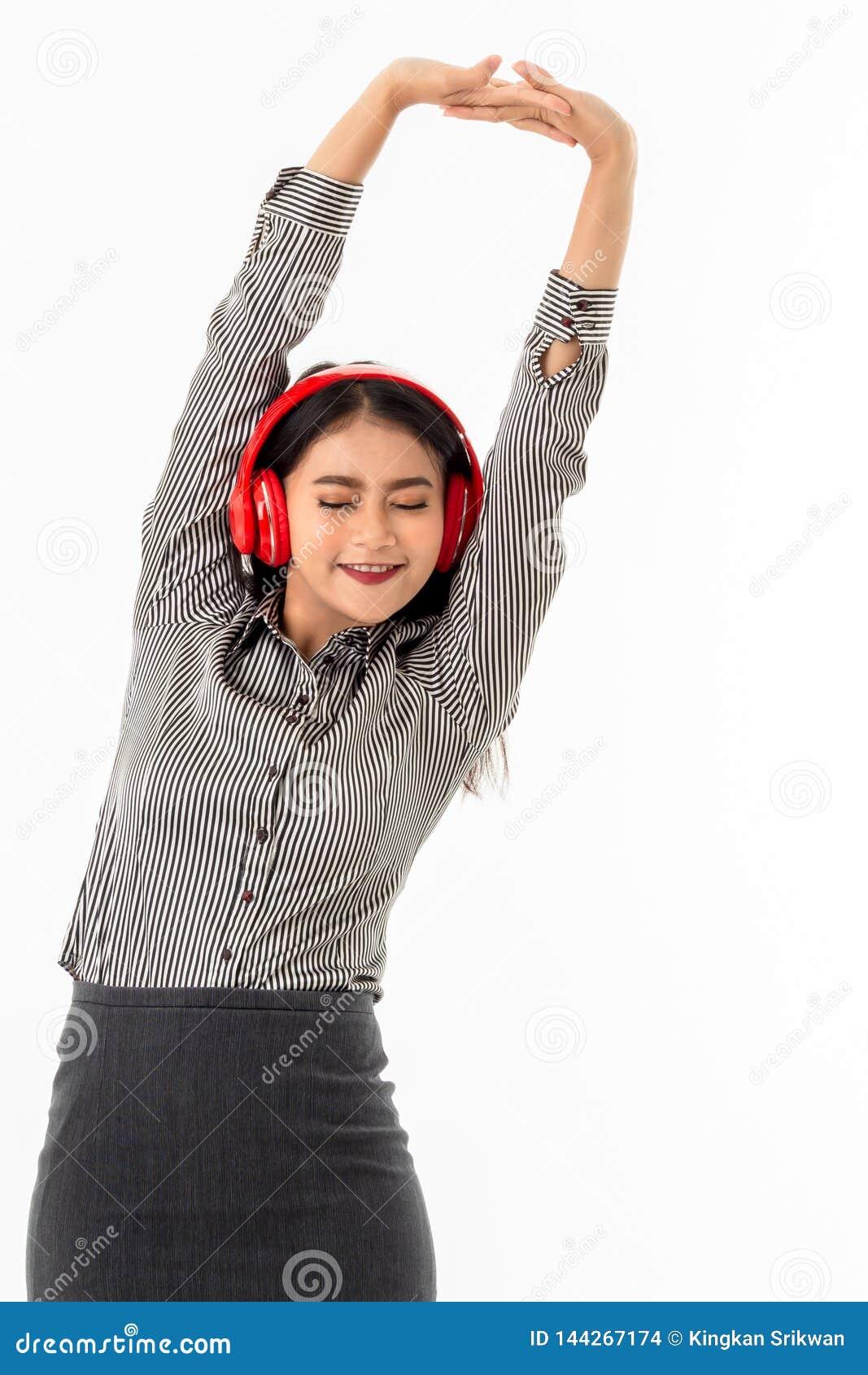 Giovane signora asiatica che indossa le cuffie rosse che allungano le sue armi sopra la sua testa