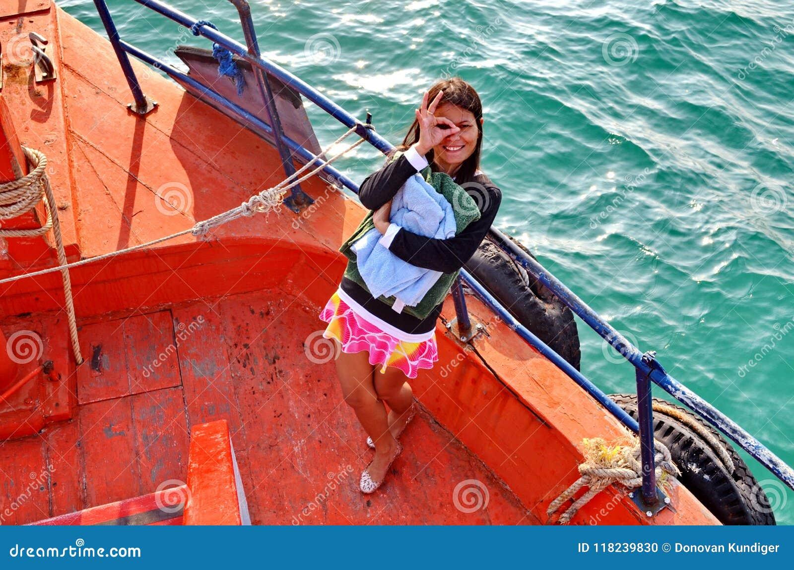 Giovane signora asiatica dà una strizzatina d occhio mentre sta alla prua di una barca