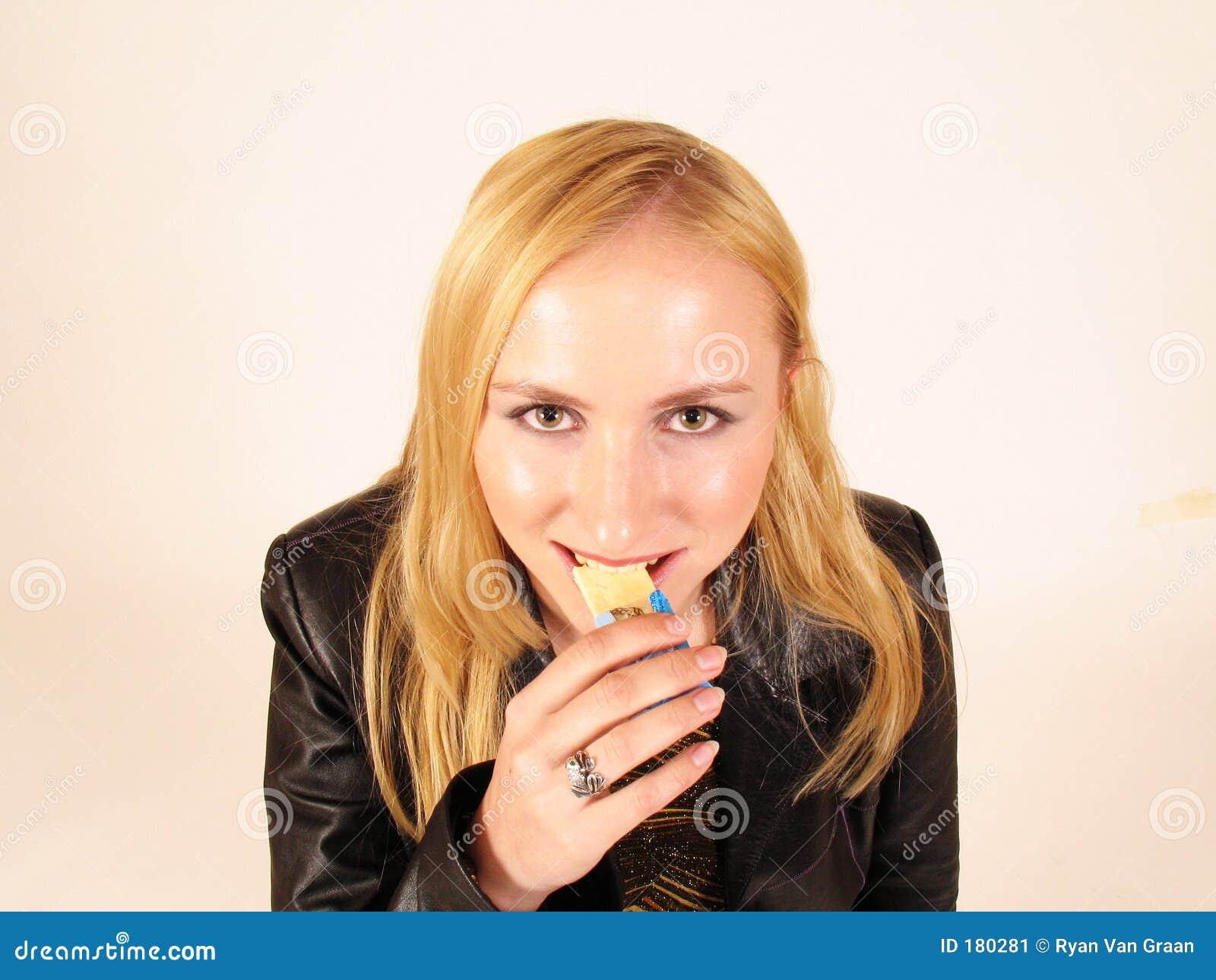 Giovane signora che mangia uno snack bar