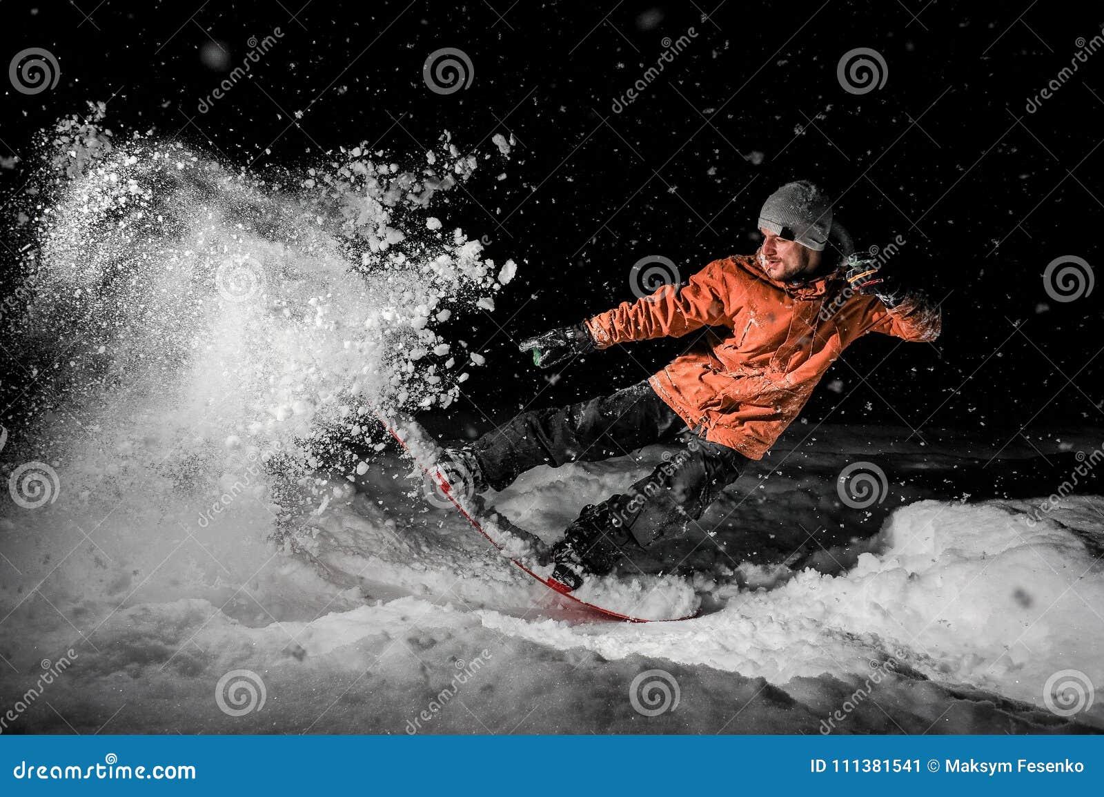Giovane snowboarder di freeride che salta nella neve alla notte