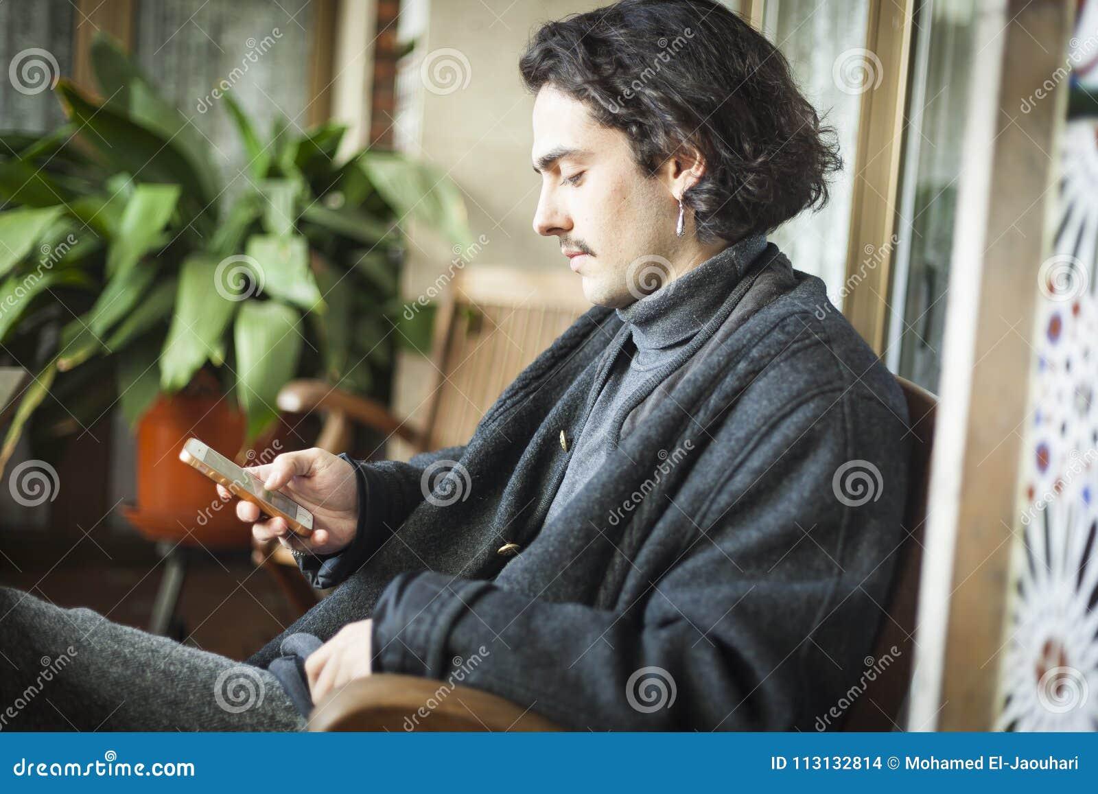 Giovane spagnolo che per mezzo dello smartphone che si siede su un terrazzo