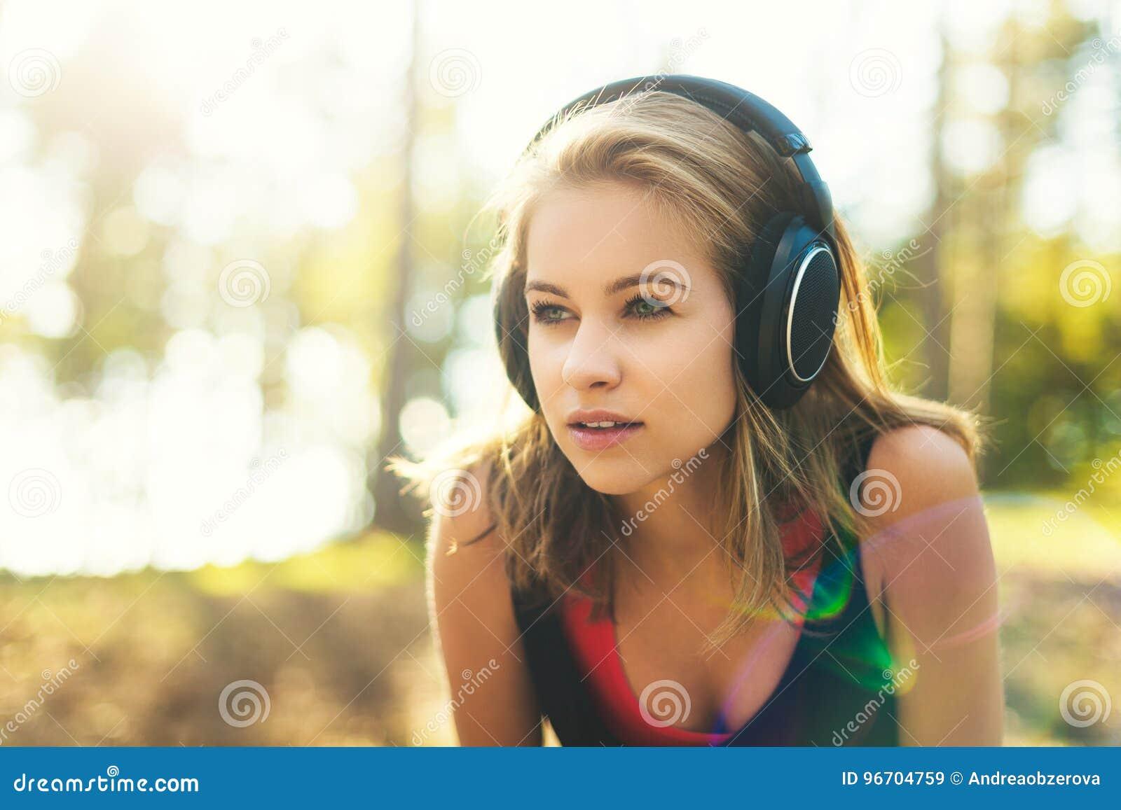 Giovane sportiva attraente che ascolta le cuffie d uso di musica Sport, forma fisica, allenamento