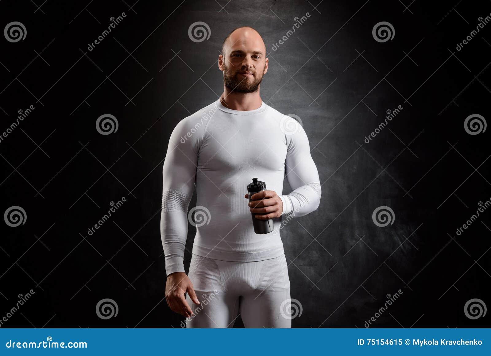 Giovane sportivo potente in abbigliamento bianco sopra fondo nero