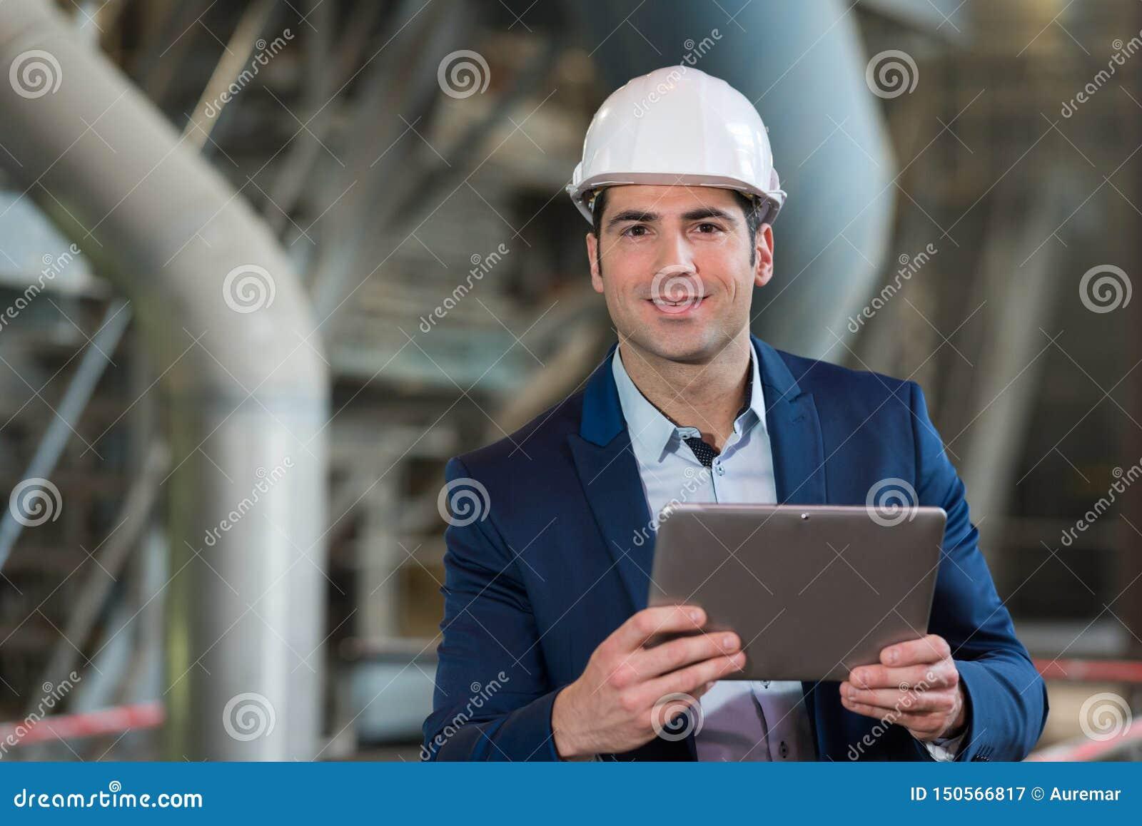 Giovane supervisore maschio che utilizza il PC della compressa nell industria