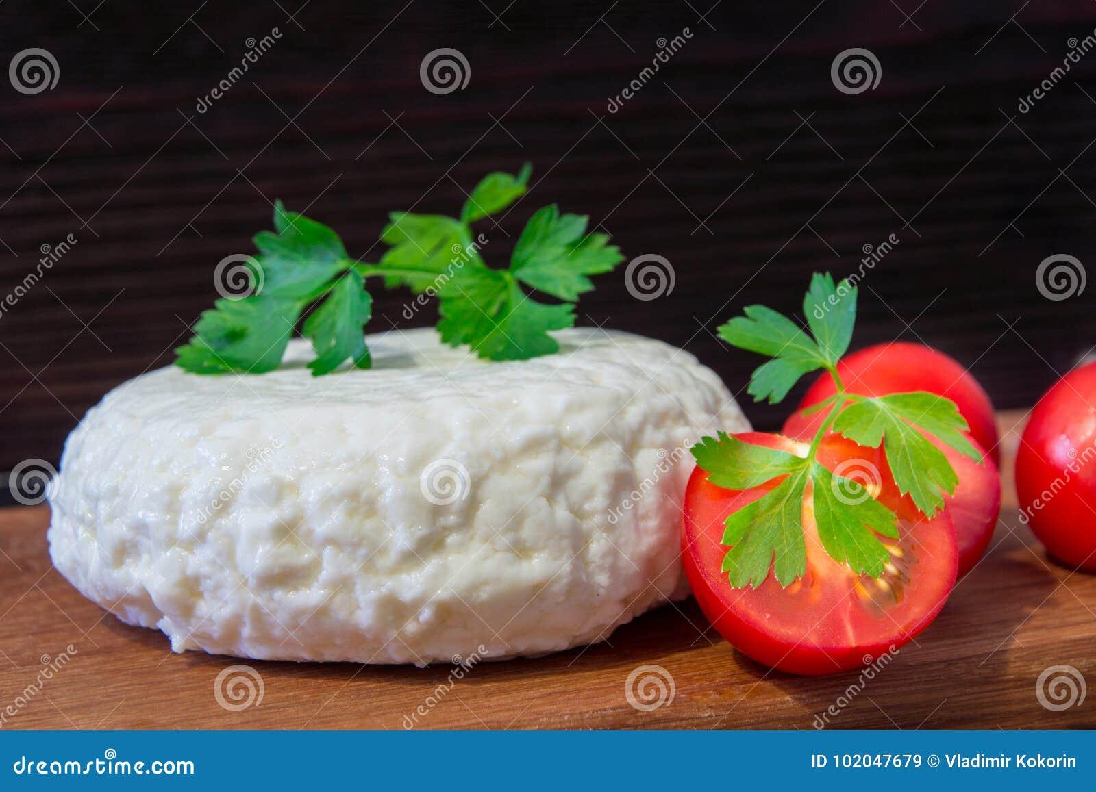 Giovane tagliere del formaggio della quercia con i pomodori ed il prezzemolo Mozarella per le pizze e le insalate