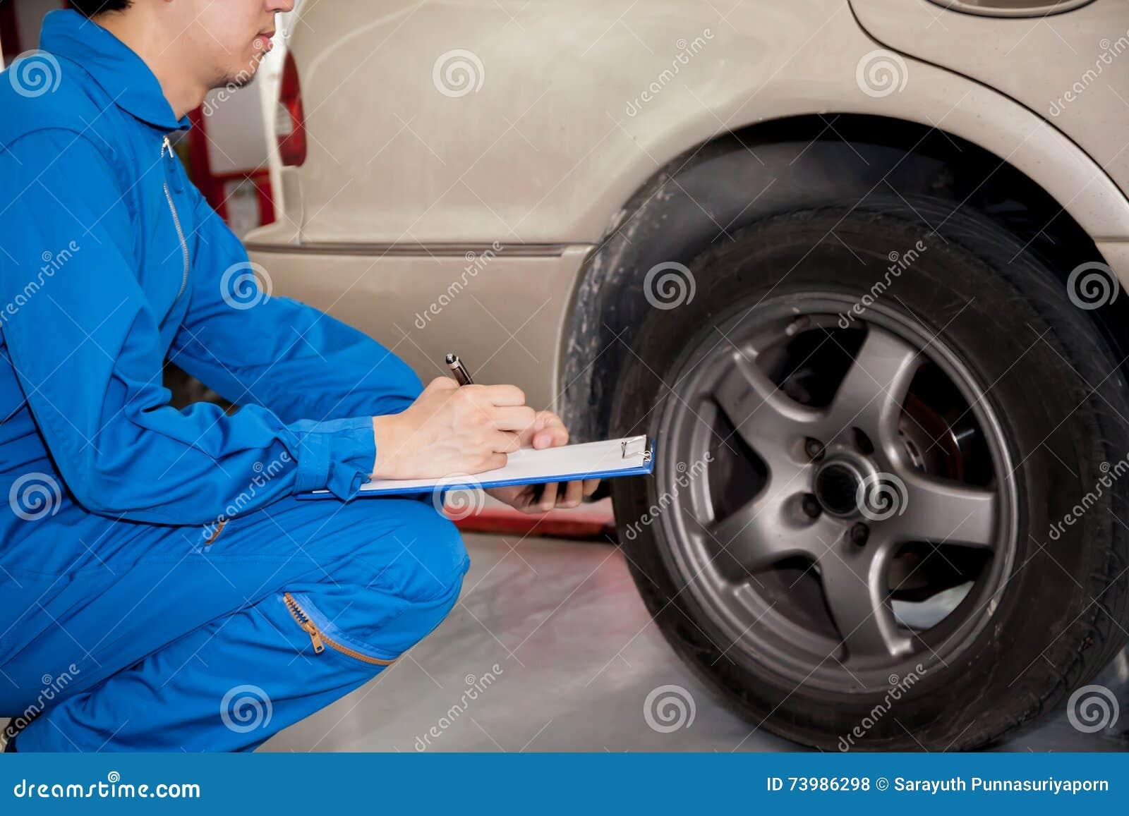 Giovane tecnico automobilistico che verifica le gomme di automobile in garage