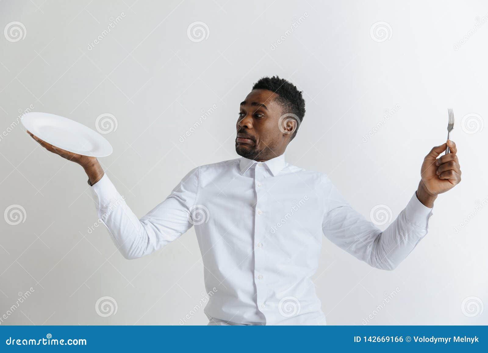 Giovane tipo afroamericano attraente di dubbio che tengono piatto vuoto e forcella isolata su fondo grigio Copi lo spazio e