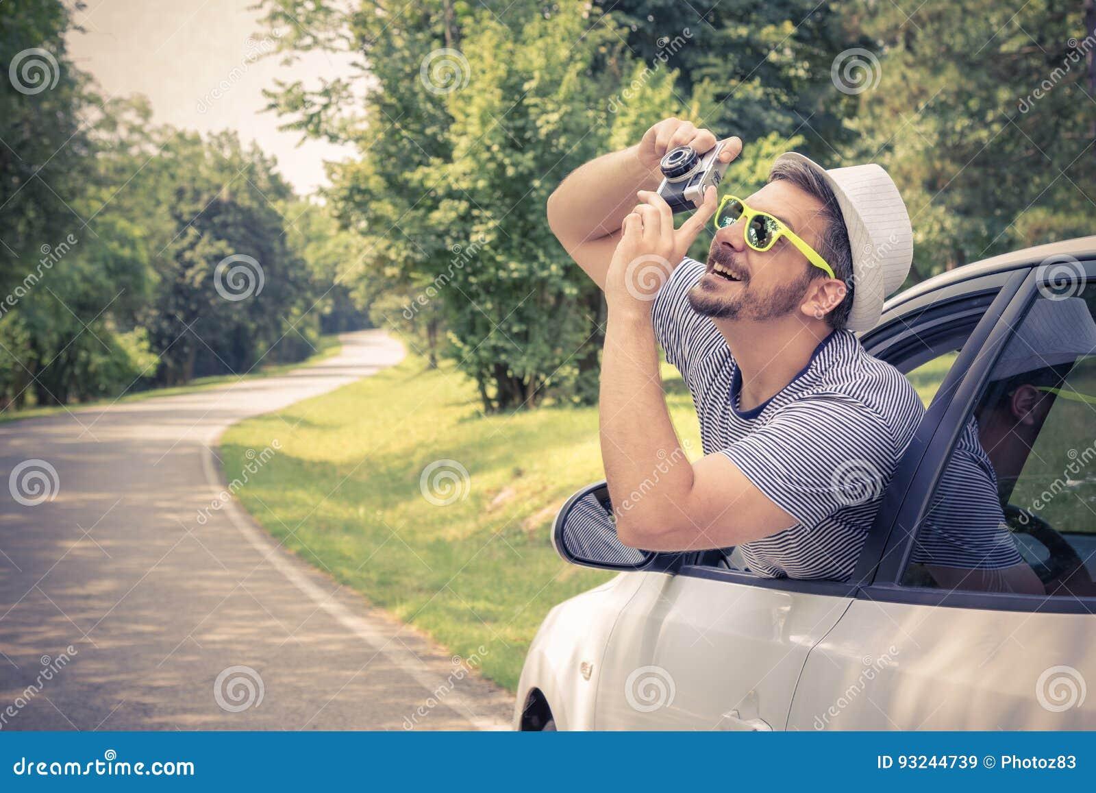 Giovane turista che prende le foto dall automobile usando retro macchina fotografica