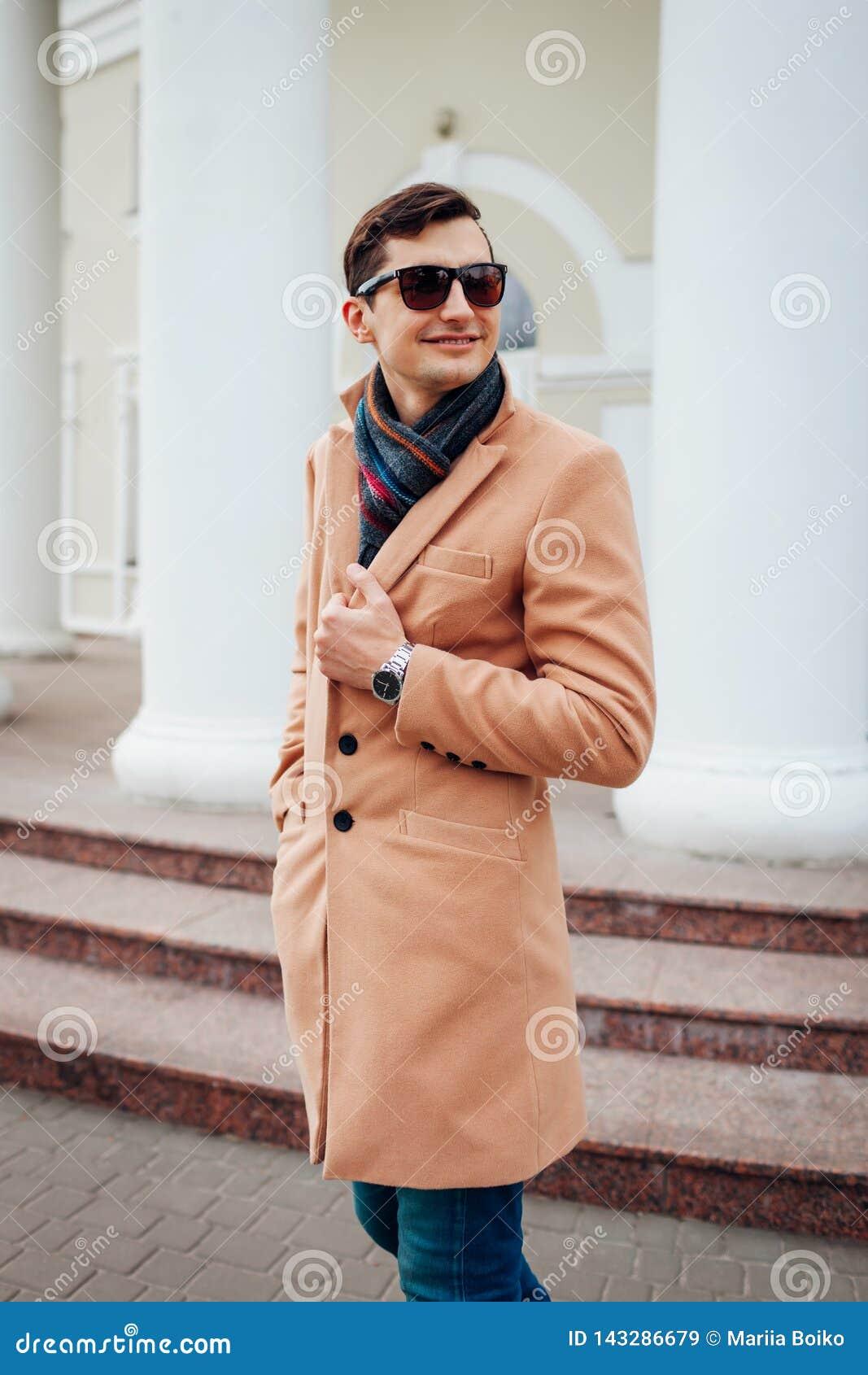 Giovane uomo alla moda che cammina nella città Tipo bello che indossa i vestiti e gli accessori classici Modo della via