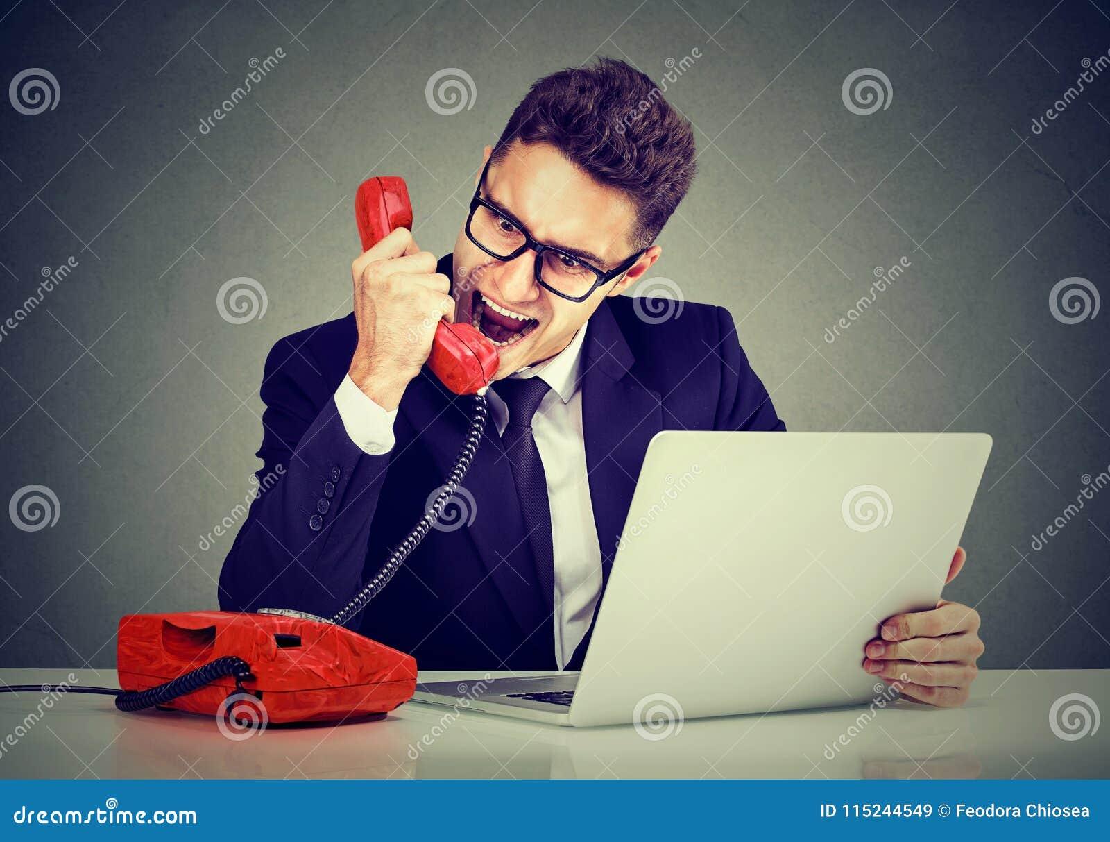 Giovane uomo arrabbiato di affari che chiama servizio di assistenza al cliente con un guasto del computer portatile che grida sul