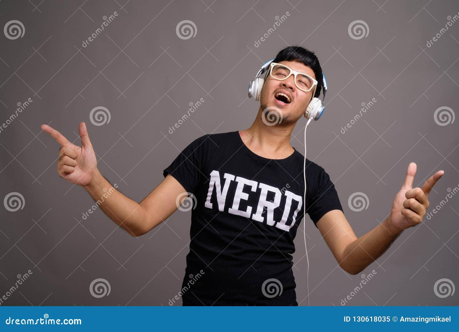 Giovane uomo asiatico del nerd che ascolta la musica contro il fondo grigio