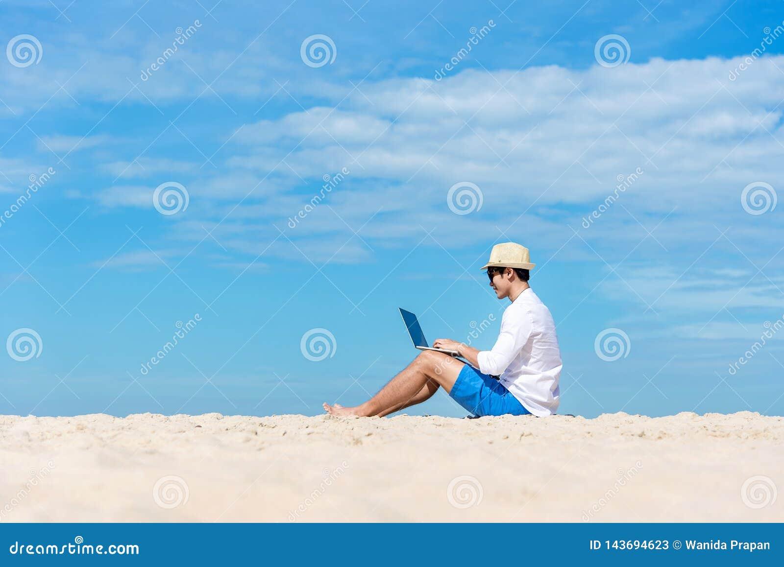 Giovane uomo asiatico di stile di vita che lavora al computer portatile mentre sedendosi freddo sulla bella spiaggia, funzionamen