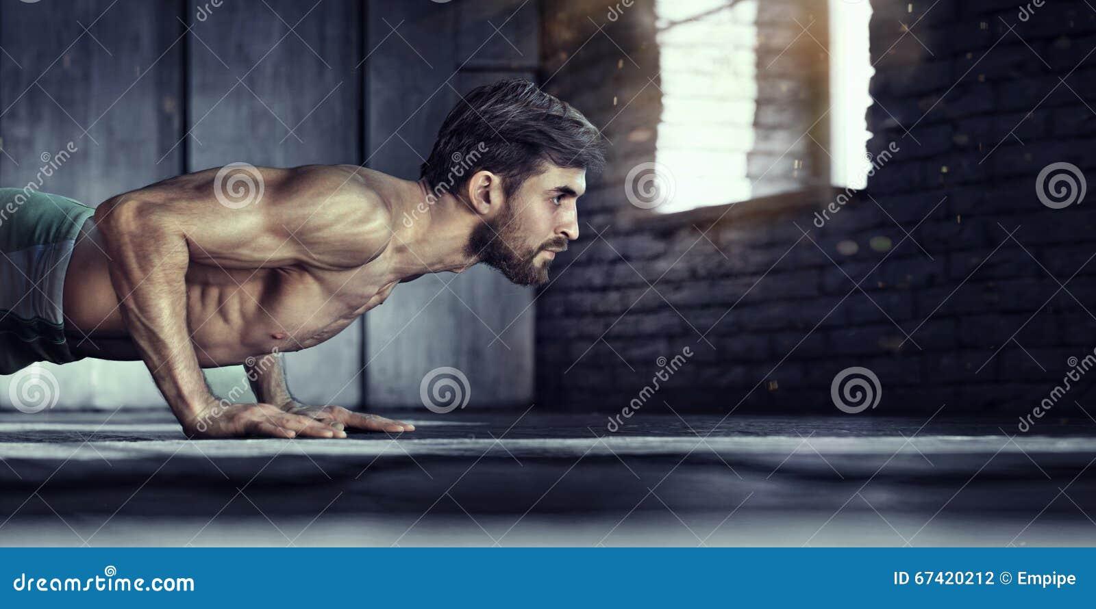 Giovane uomo atletico che fa spinta-UPS