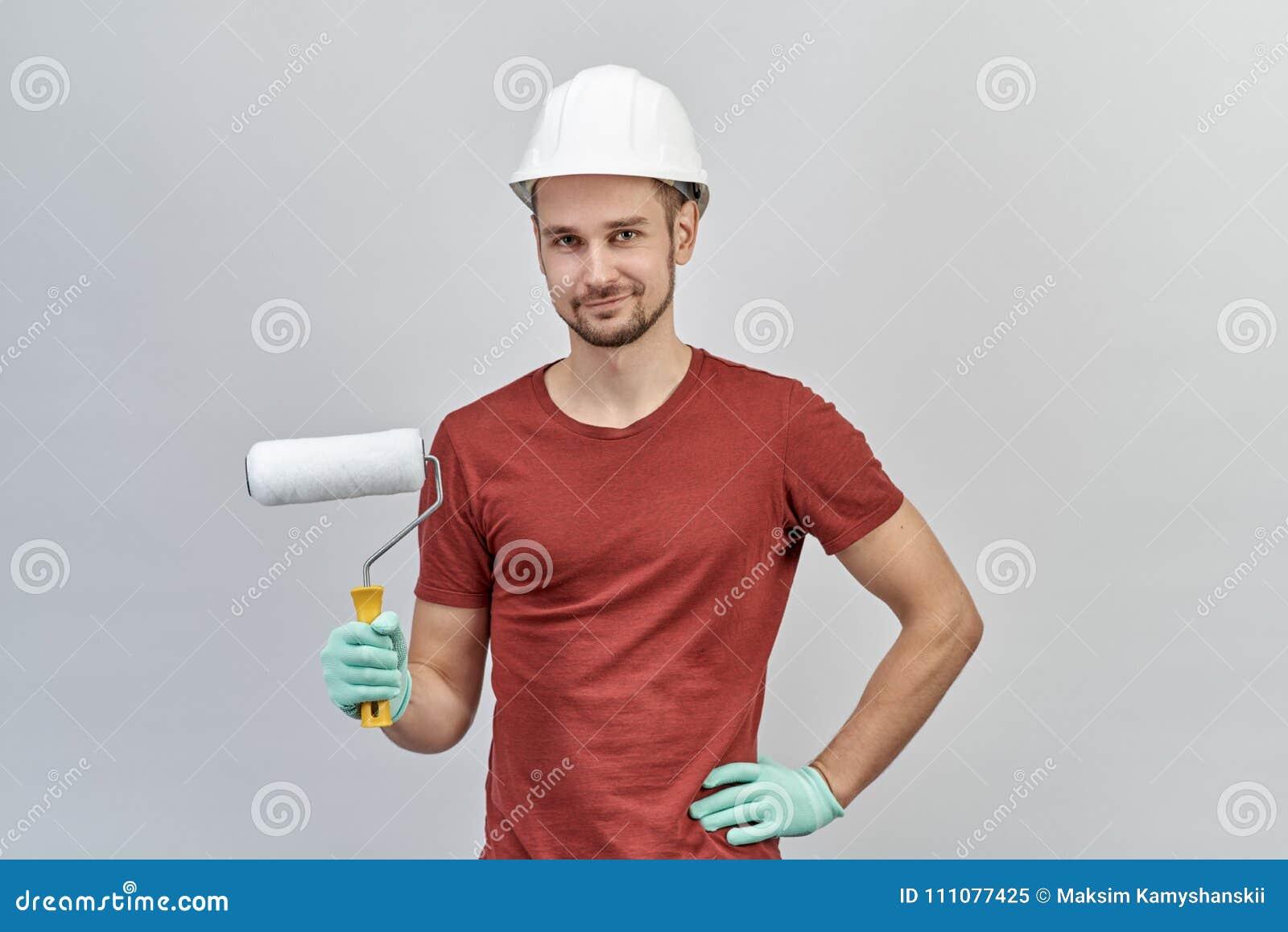 Giovane uomo attraente in camicia rossa, in casco protettivo bianco ed in guanti tenenti rullo per dipingere con l espressione fe