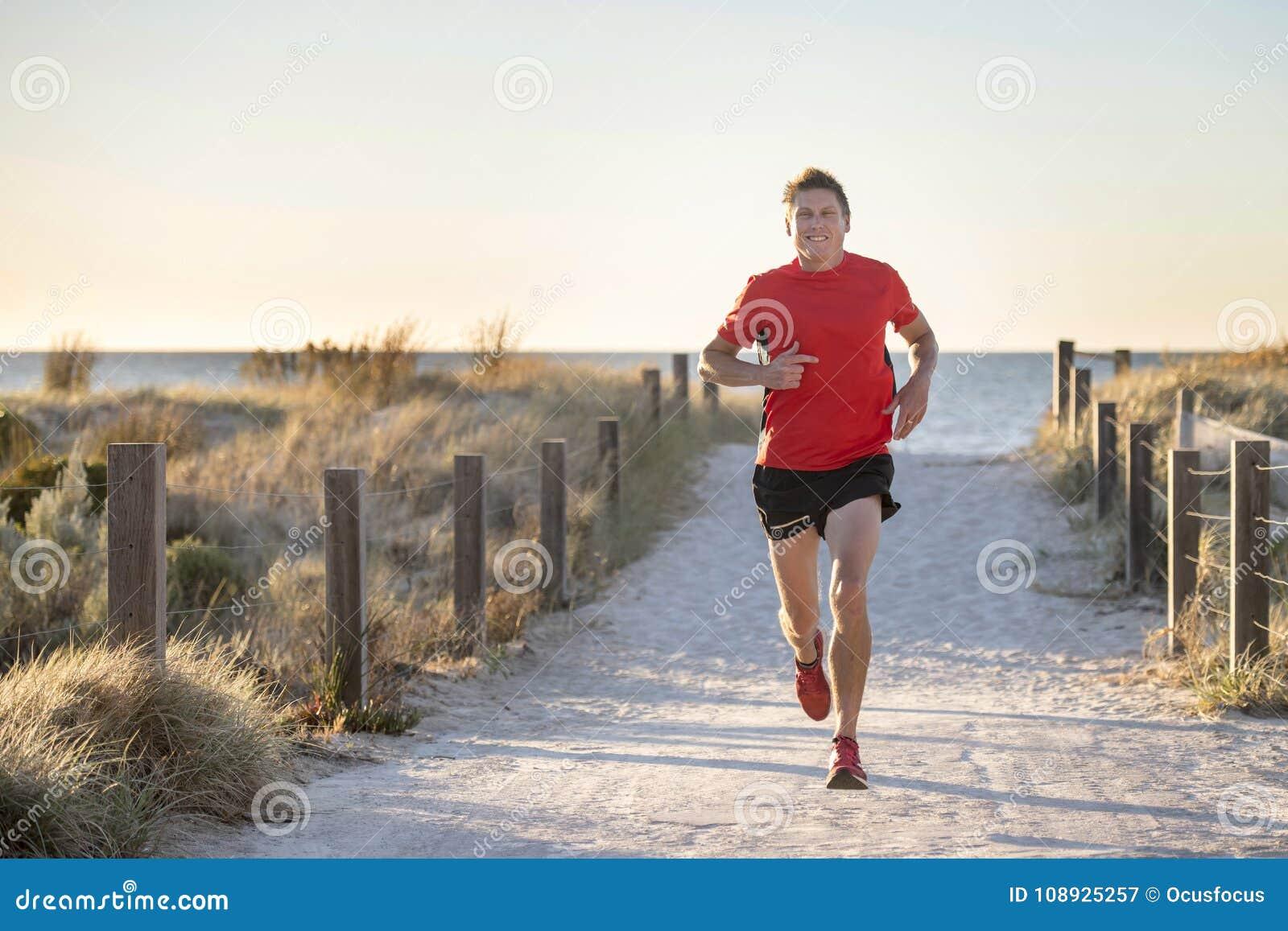Giovane uomo attraente e felice del corridore di sport con la misura ed il forte addestramento sano del corpo fuori dalla pista d