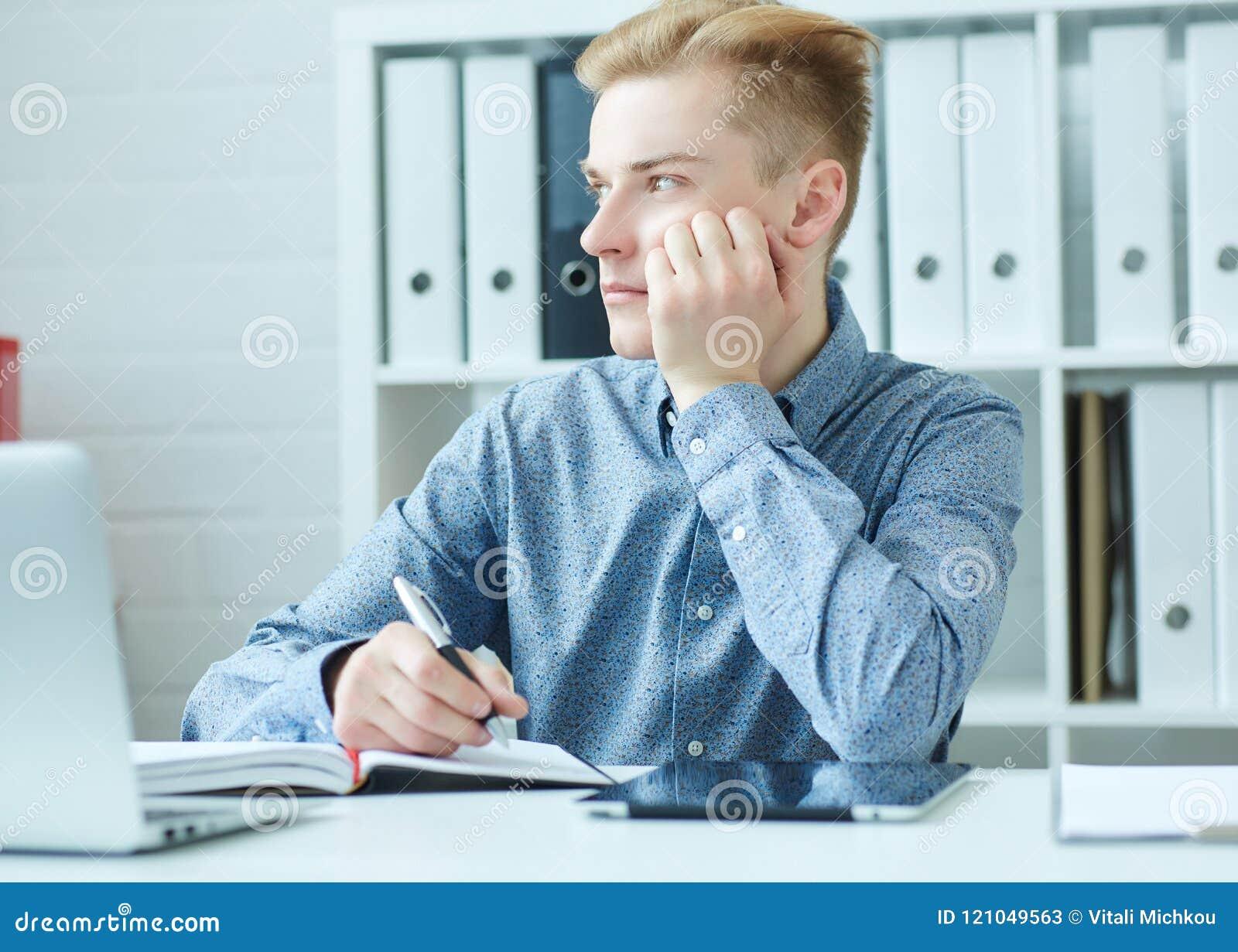 Giovane uomo bello di affari che si siede al dask con il computer portatile e che esamina la finestra