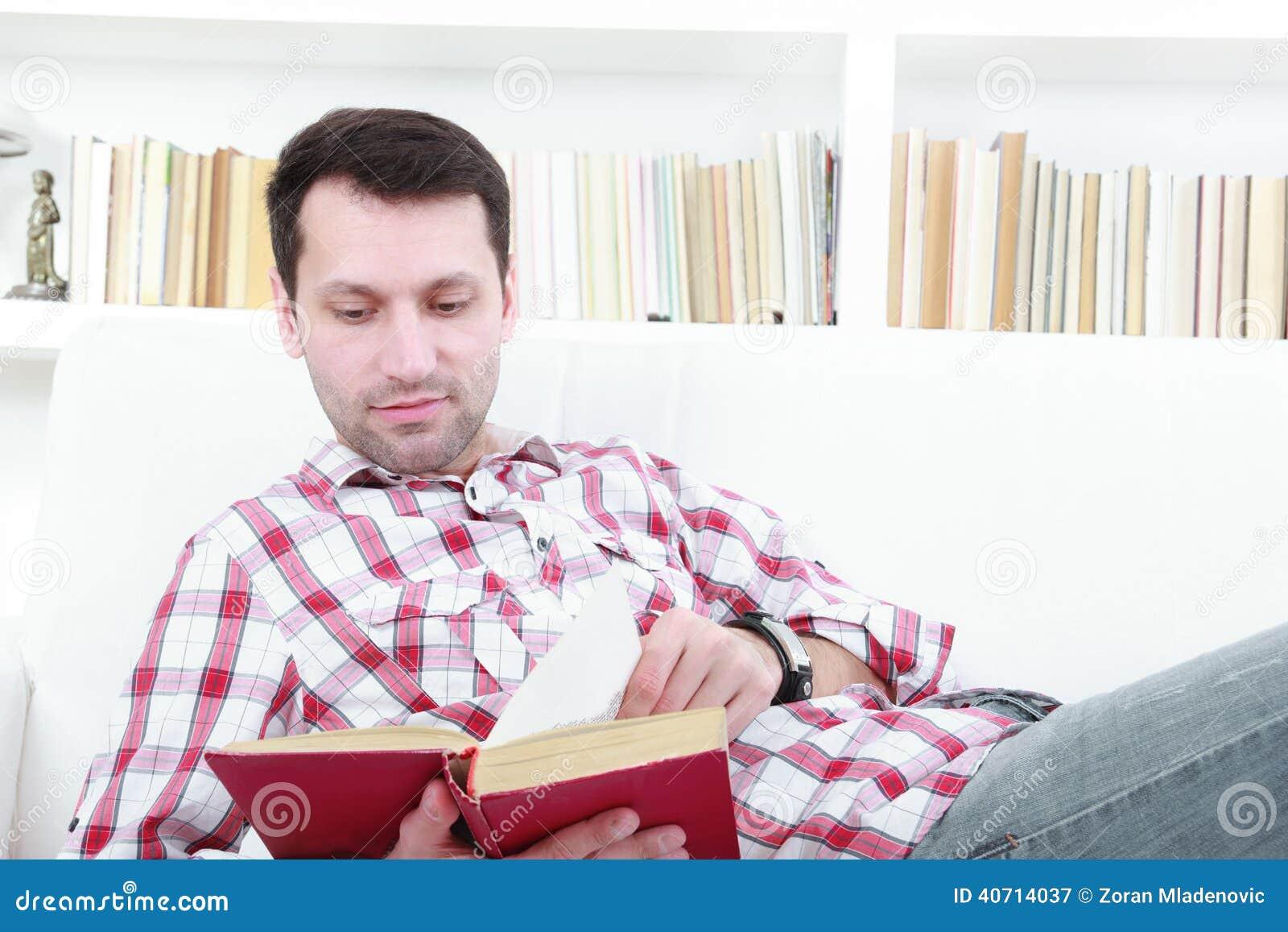 Giovane uomo casuale che legge un libro che si rilassa sul sofà