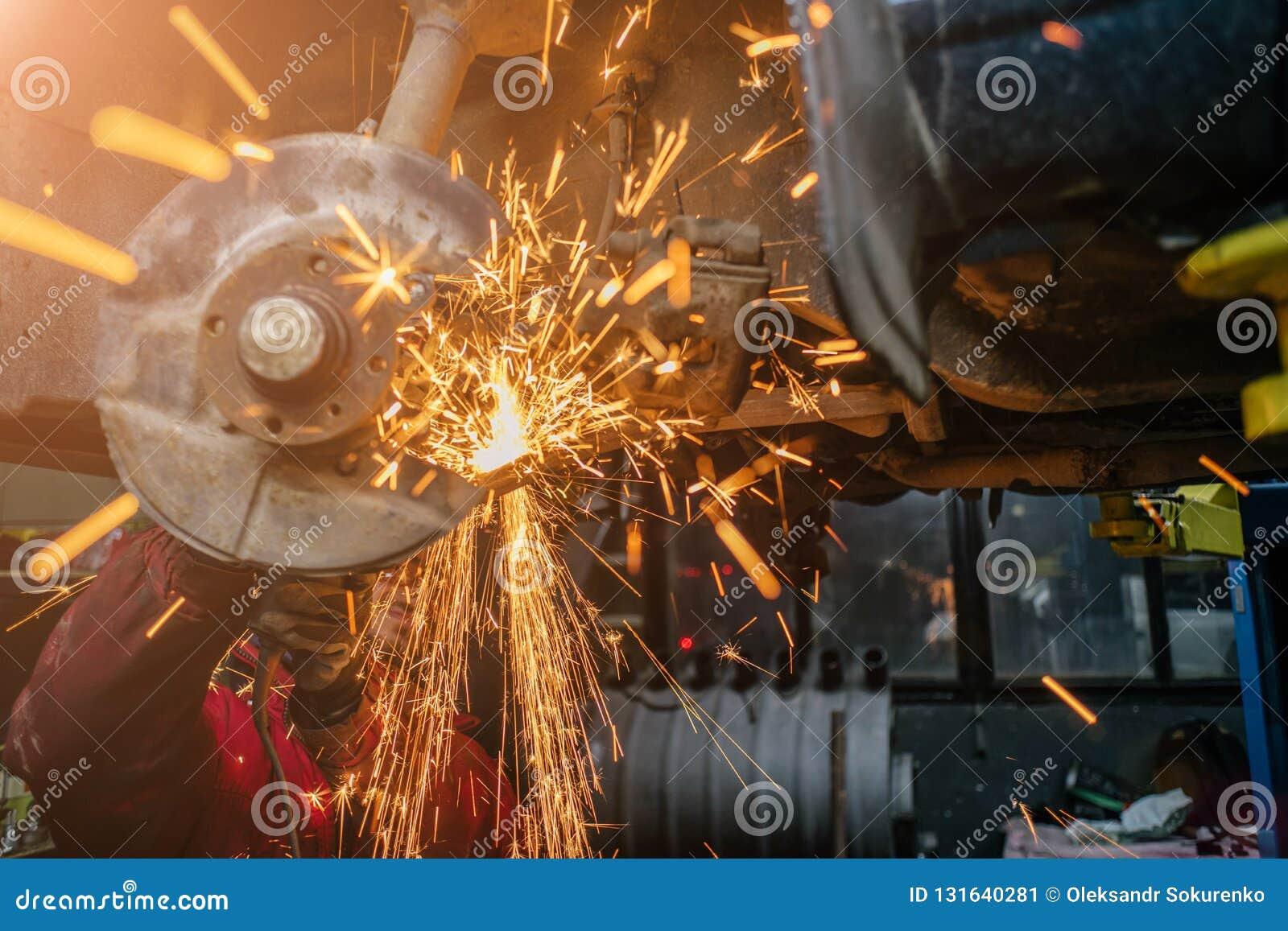Giovane uomo caucasico in indumenti da lavoro rossi che riparano automobile con la taglierina di angolo