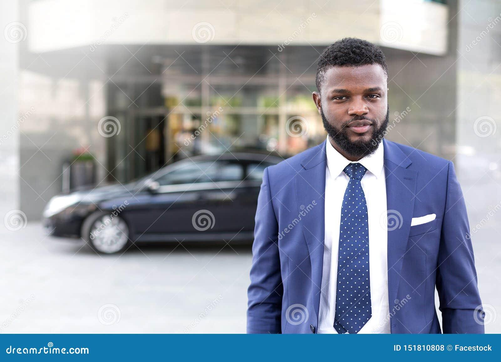 Giovane uomo d affari africano che lascia la sua automobile nera sui locali di ufficio
