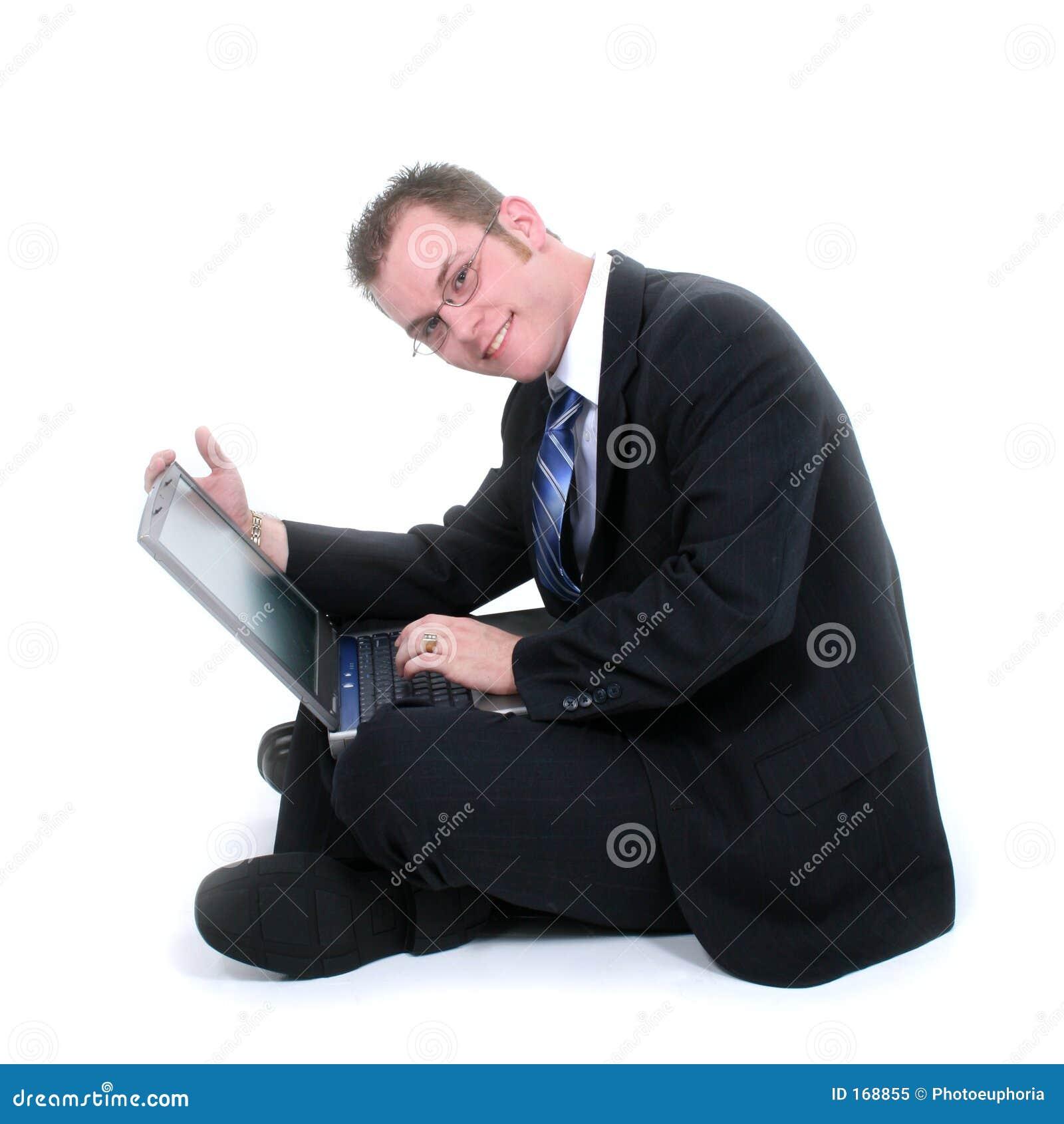 Giovane uomo d affari attraente che si siede sul pavimento con il computer portatile