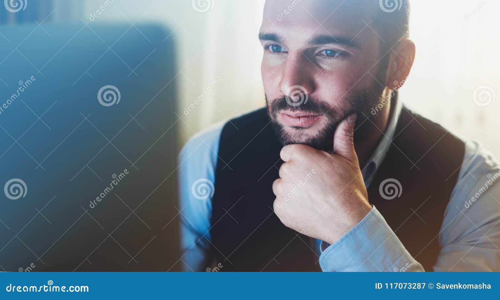 Giovane uomo d affari barbuto che lavora all ufficio moderno Sguardo di pensiero dell uomo del consulente in computer del monitor