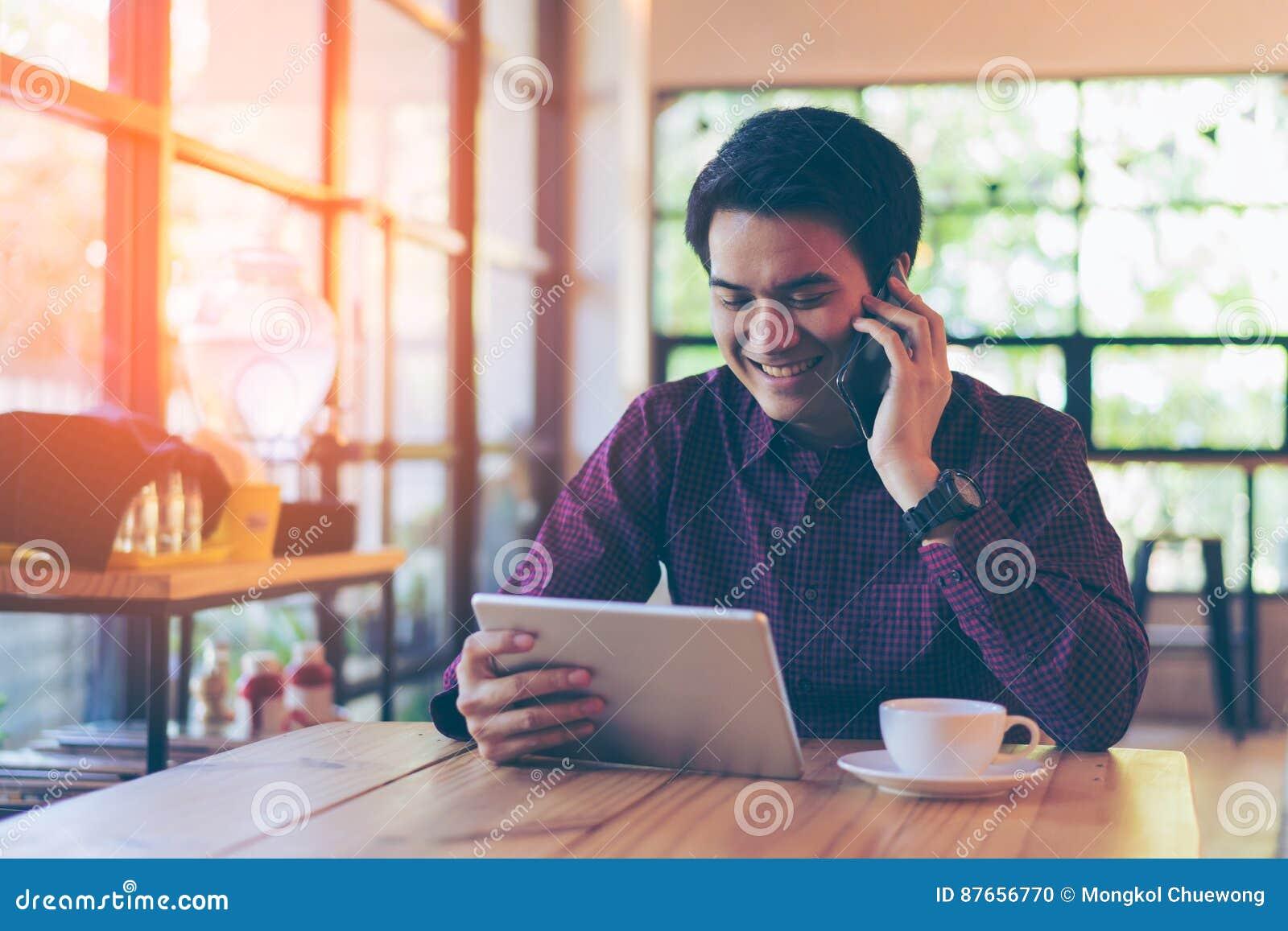 Giovane uomo d affari bello asiatico che sorride mentre leggendo la sua tavola