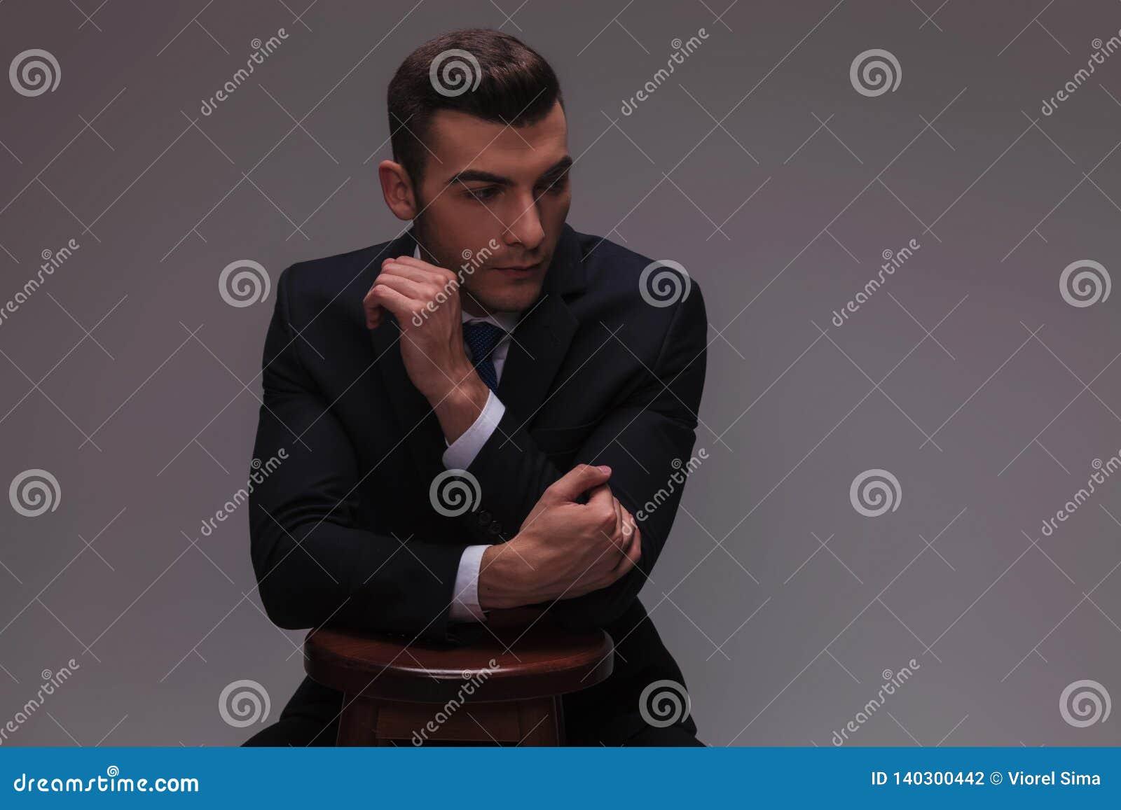 Giovane uomo d affari che è alla moda con le mani su una sedia