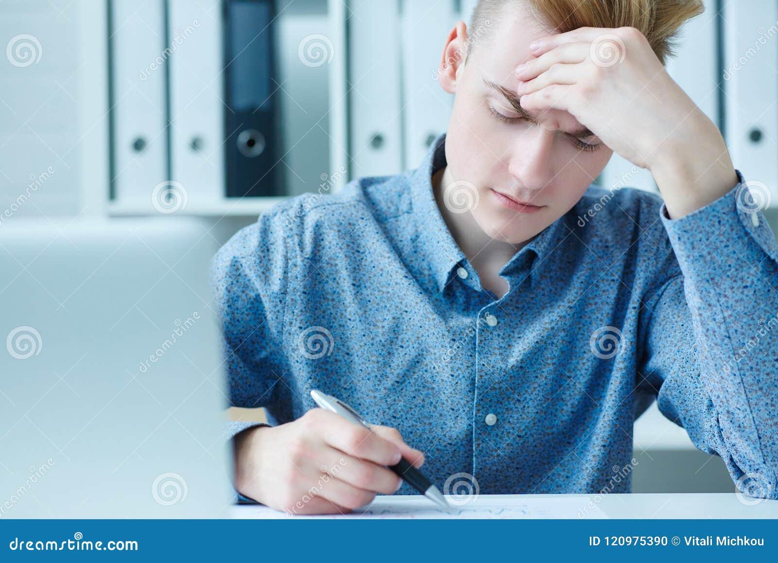 Giovane uomo d affari maschio che prende le note sul computer portatile, lavorando con il grafico di dati, sedentesi nell ufficio