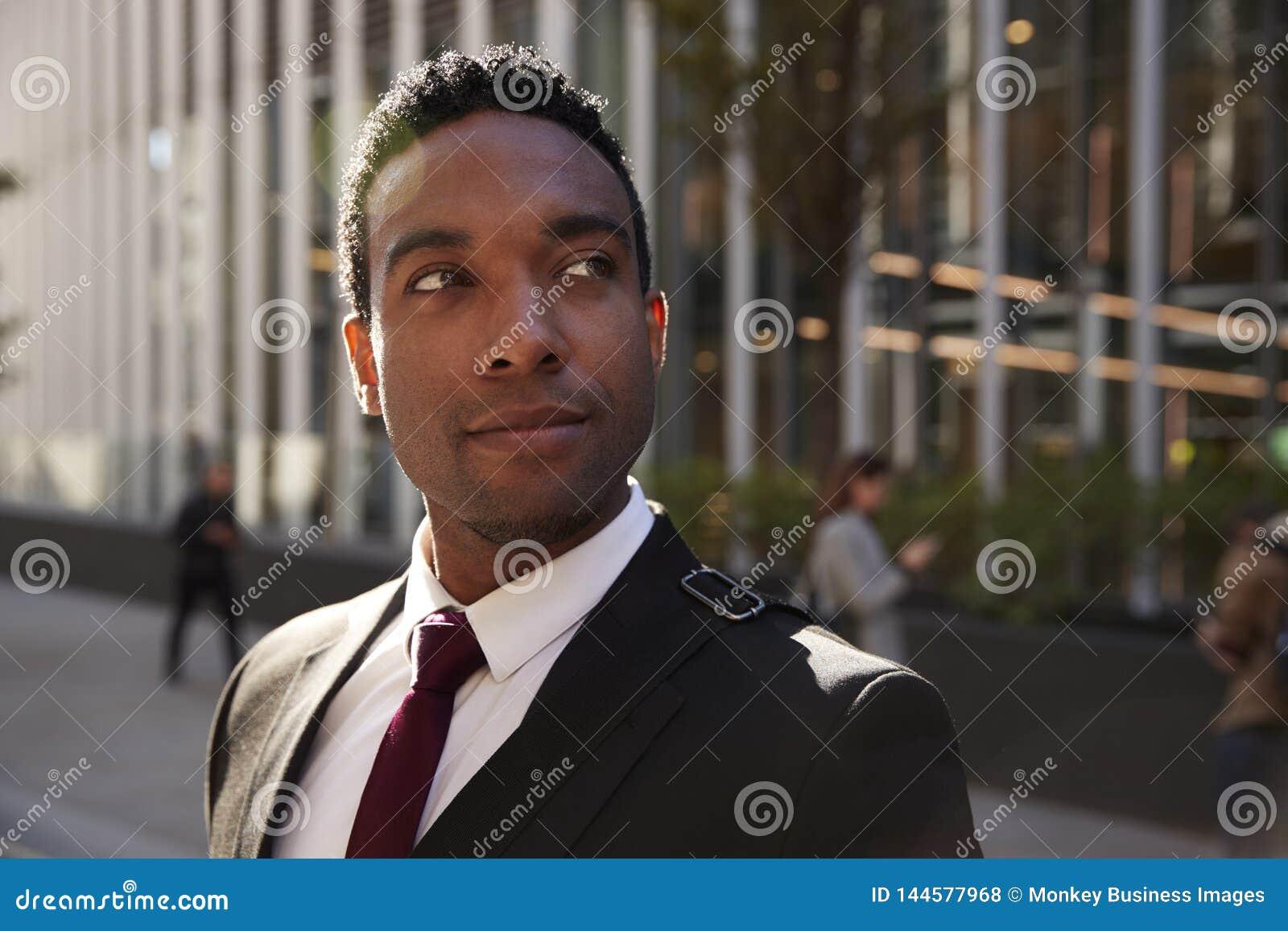 Giovane uomo d affari nero che indossa condizione nera del vestito sulla via che sorride, distogliendo lo sguardo, fine su