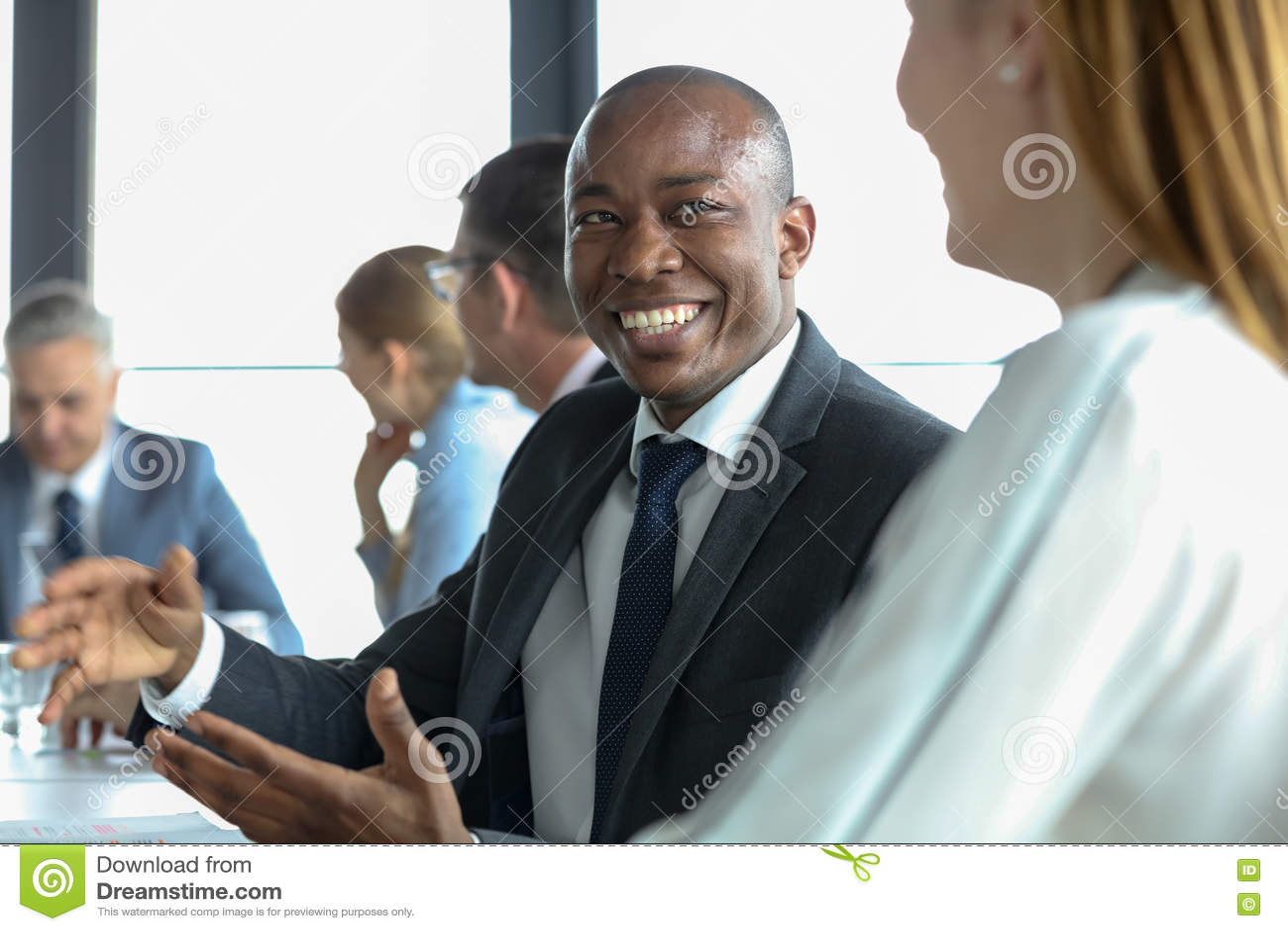 Giovane uomo d affari sorridente che discute con il collega femminile nella sala riunioni