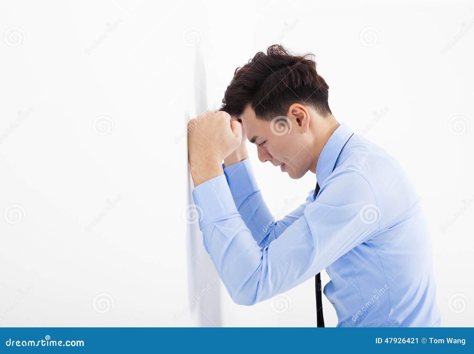 Giovane uomo depresso di affari che pende alla parete in ufficio