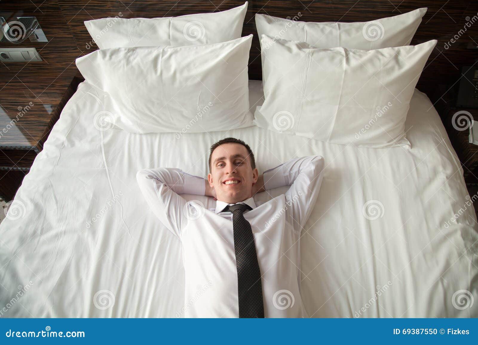 Giovane uomo di affari che si rilassa a letto