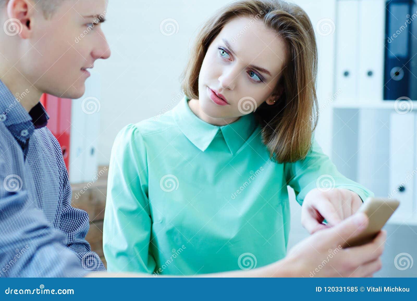 Giovane uomo di affari e signora di affari che guarda qualcosa sullo schermo dello smartphone