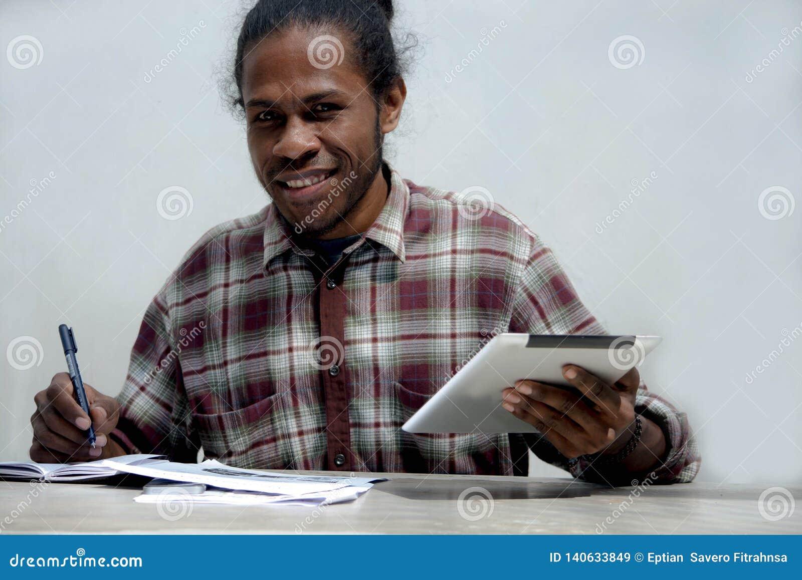 Giovane uomo di colore sorridente che lavora e che studia giudicando computer portatile e penna che fanno compito