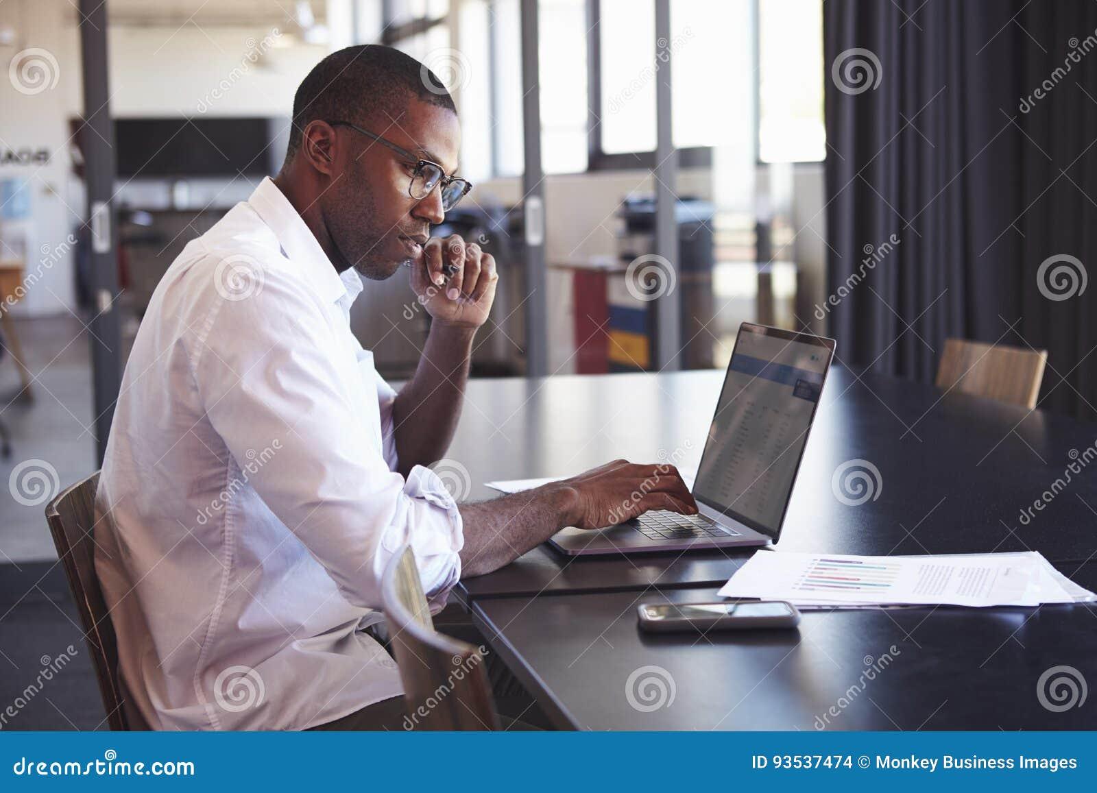 Giovane uomo di colore in vetri d uso facendo uso del computer portatile in ufficio
