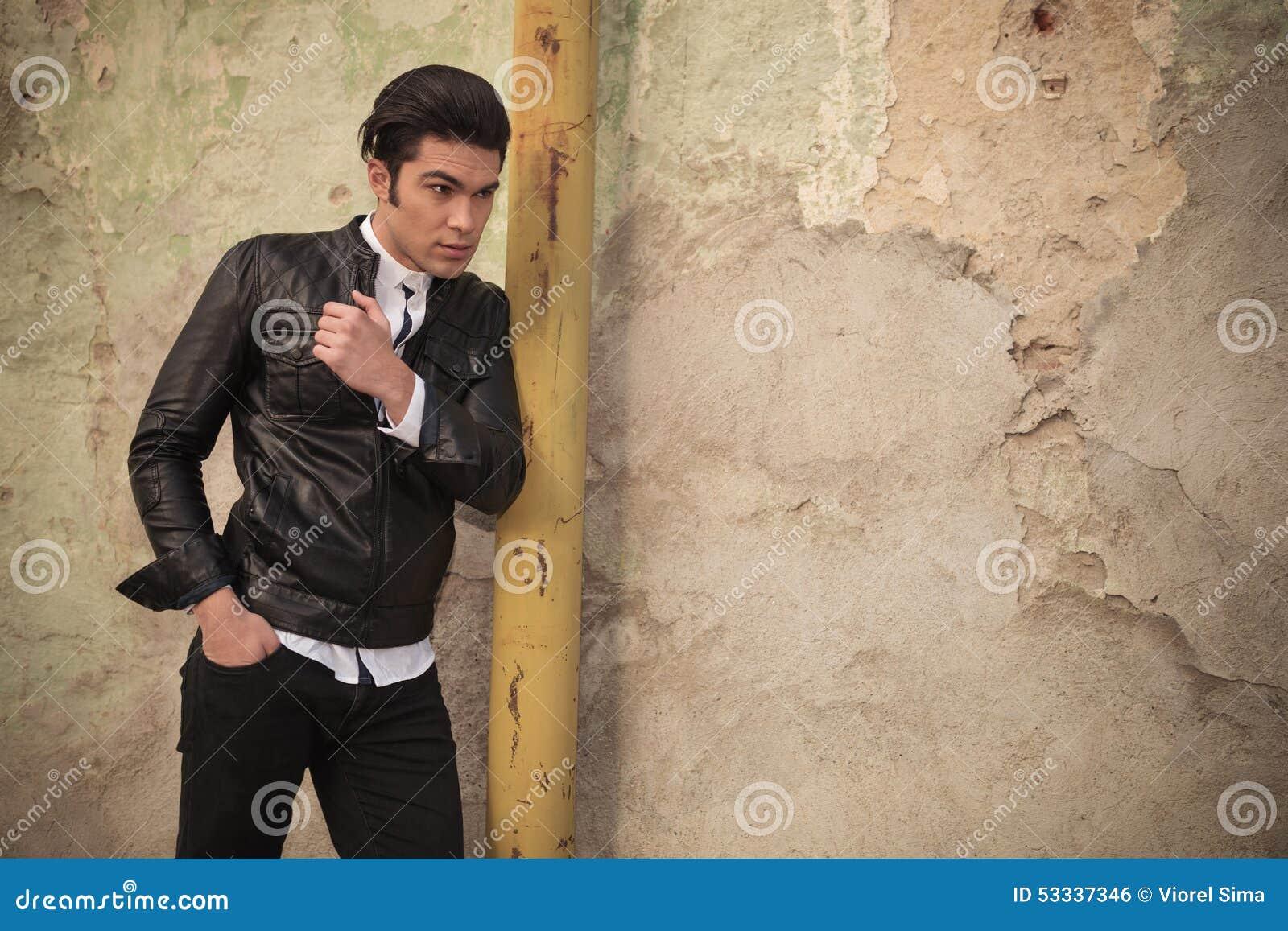 Giovane uomo di modo che tiene una mano in sua tasca