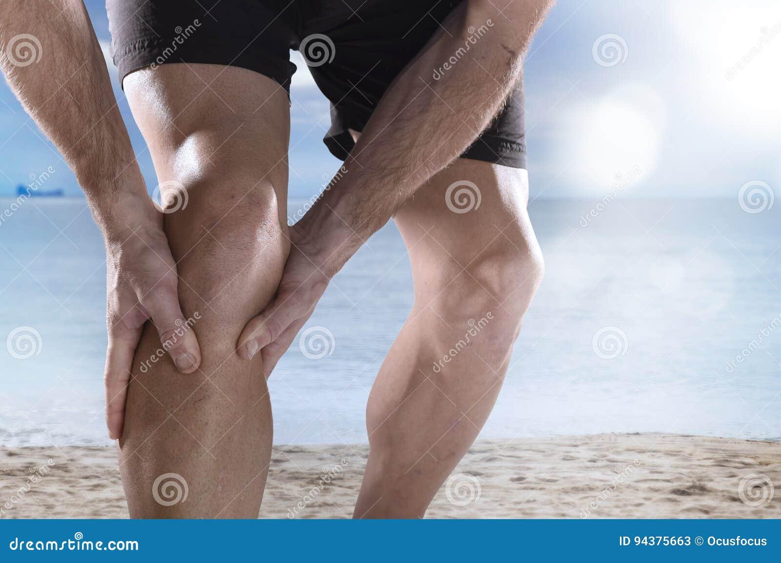Giovane uomo di sport con le gambe atletiche che tengono ginocchio nel funzionamento di sofferenza di lesione del muscolo di dolo