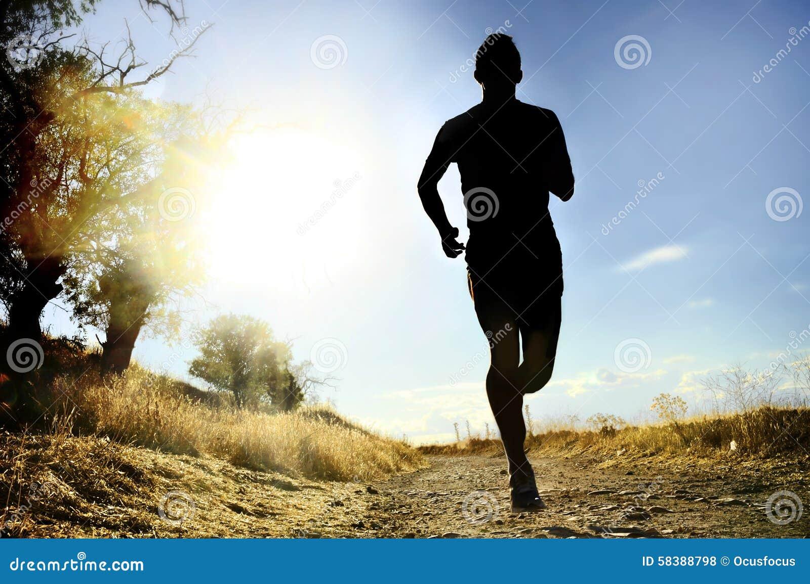 Giovane uomo di sport della siluetta anteriore che governa allenamento del paese trasversale al tramonto di estate