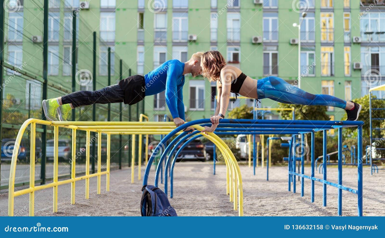 Giovane uomo e donna attrective del crossfit che risolvono sullo sportsground