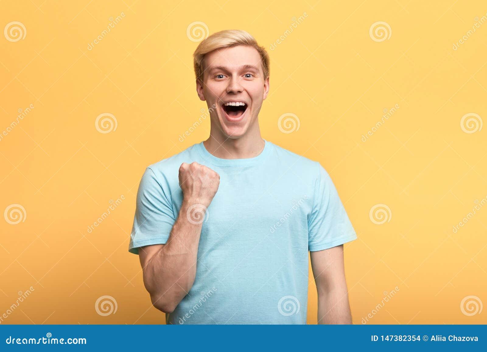 Giovane uomo emozionale splendido positivo che alza i pugni chiusi evviva nel gesto
