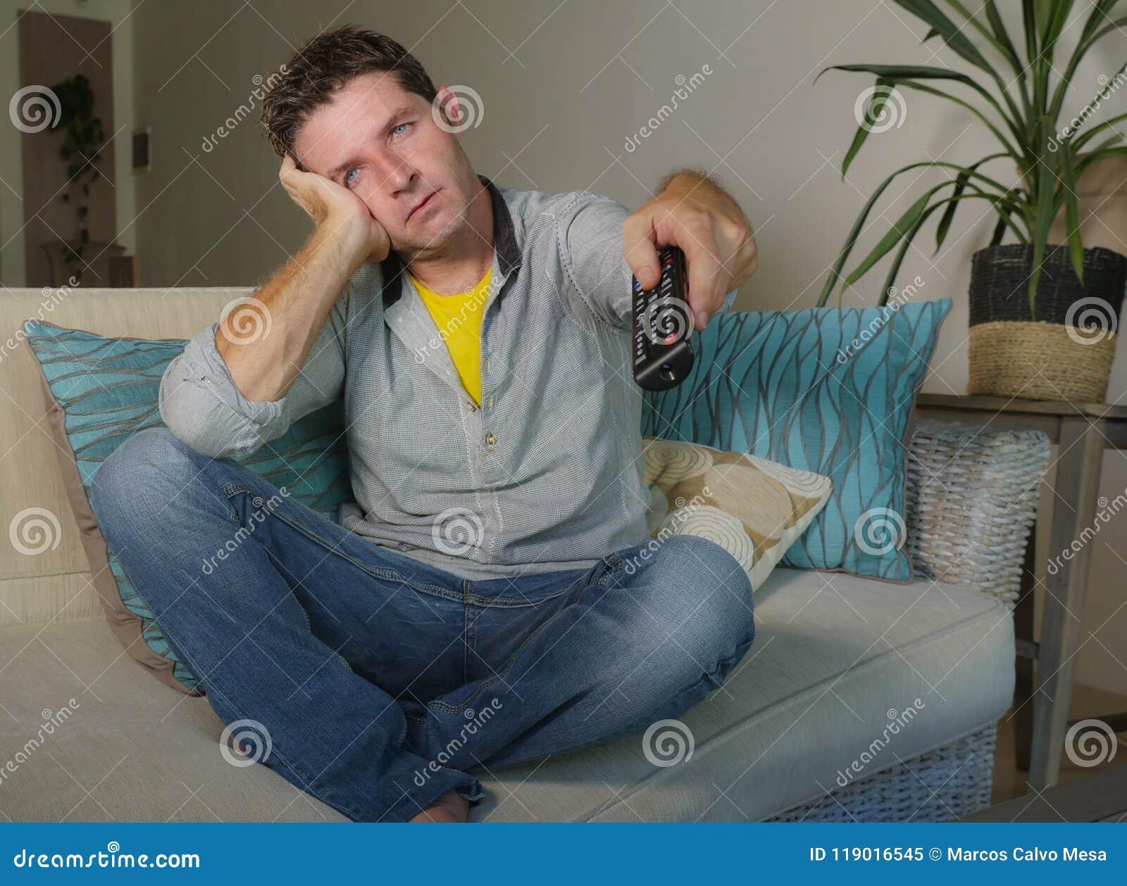 Giovane uomo infelice attraente in abbigliamento casual a casa annoiato e nel film di sorveglianza frustrato della TV sullo strat