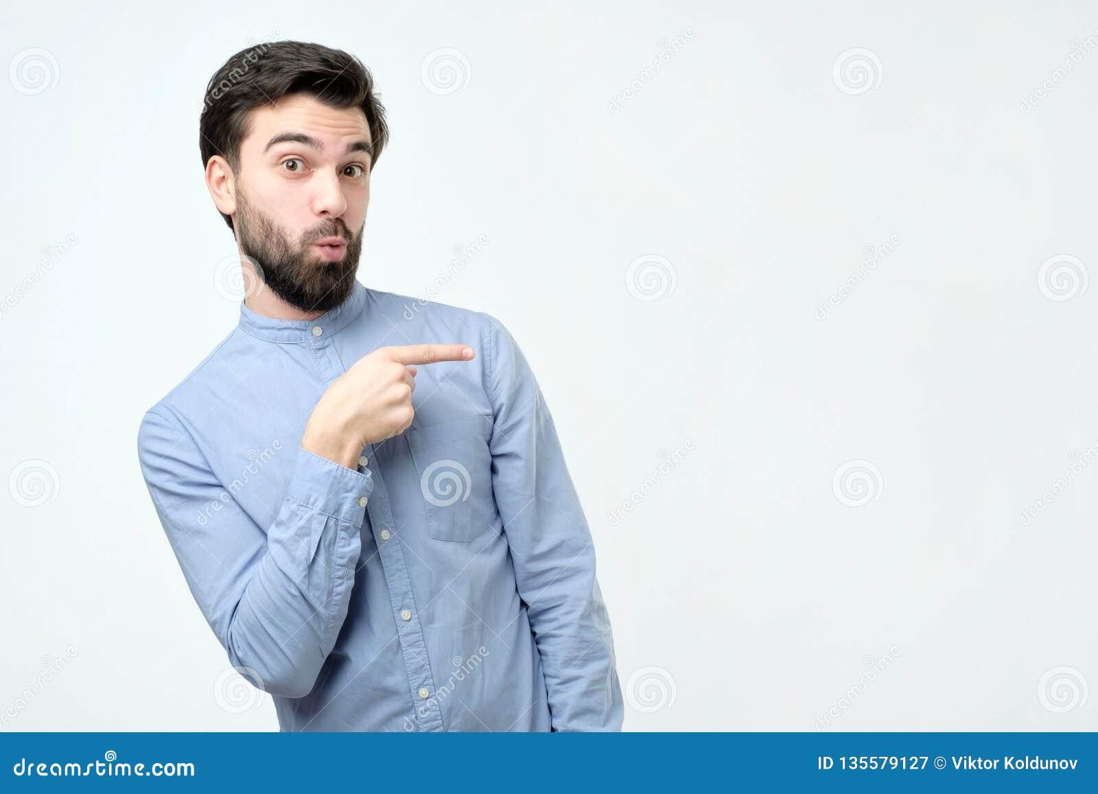 Giovane uomo ispanico bello alla moda che indica da parte