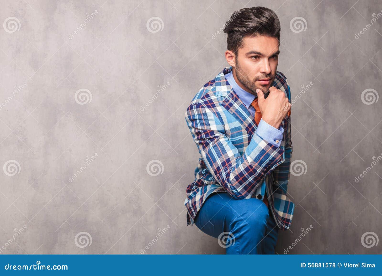 Giovane uomo premuroso di affari che pende la sua mano sulla sua gamba