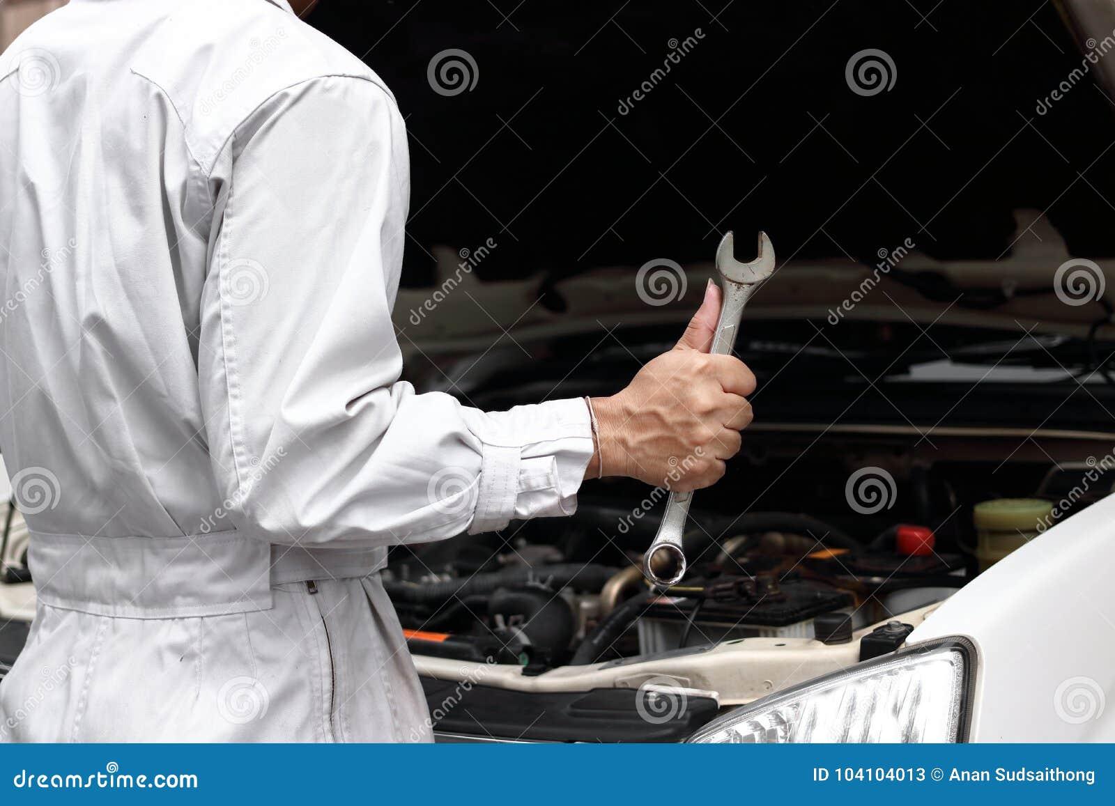 Giovane uomo professionale del meccanico in uniforme con la chiave che diagnostica motore contro il cappuccio aperto al garage di