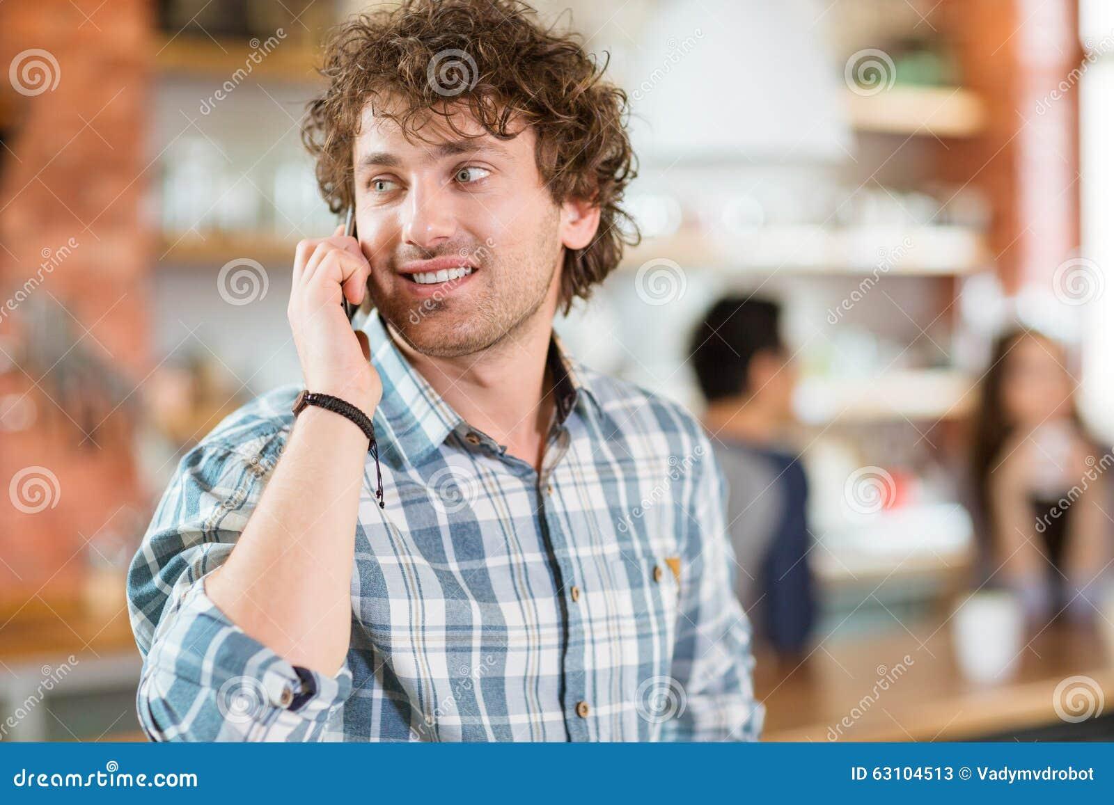 Giovane uomo riccio moderno felice attraente che parla sul telefono cellulare